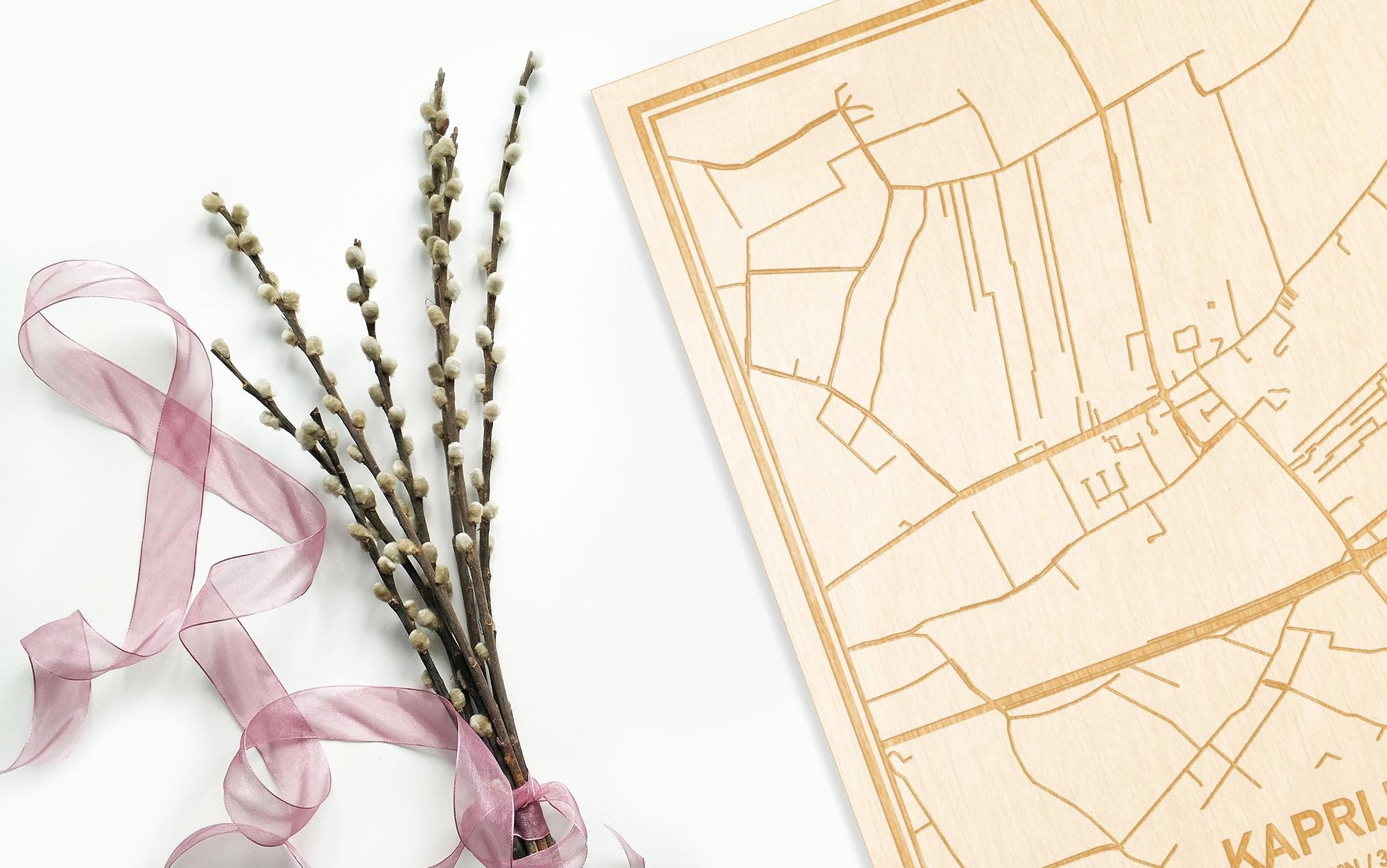 Hier ligt de houten plattegrond Kaprijke naast een bloemetje als gepersonaliseerd cadeau voor haar.