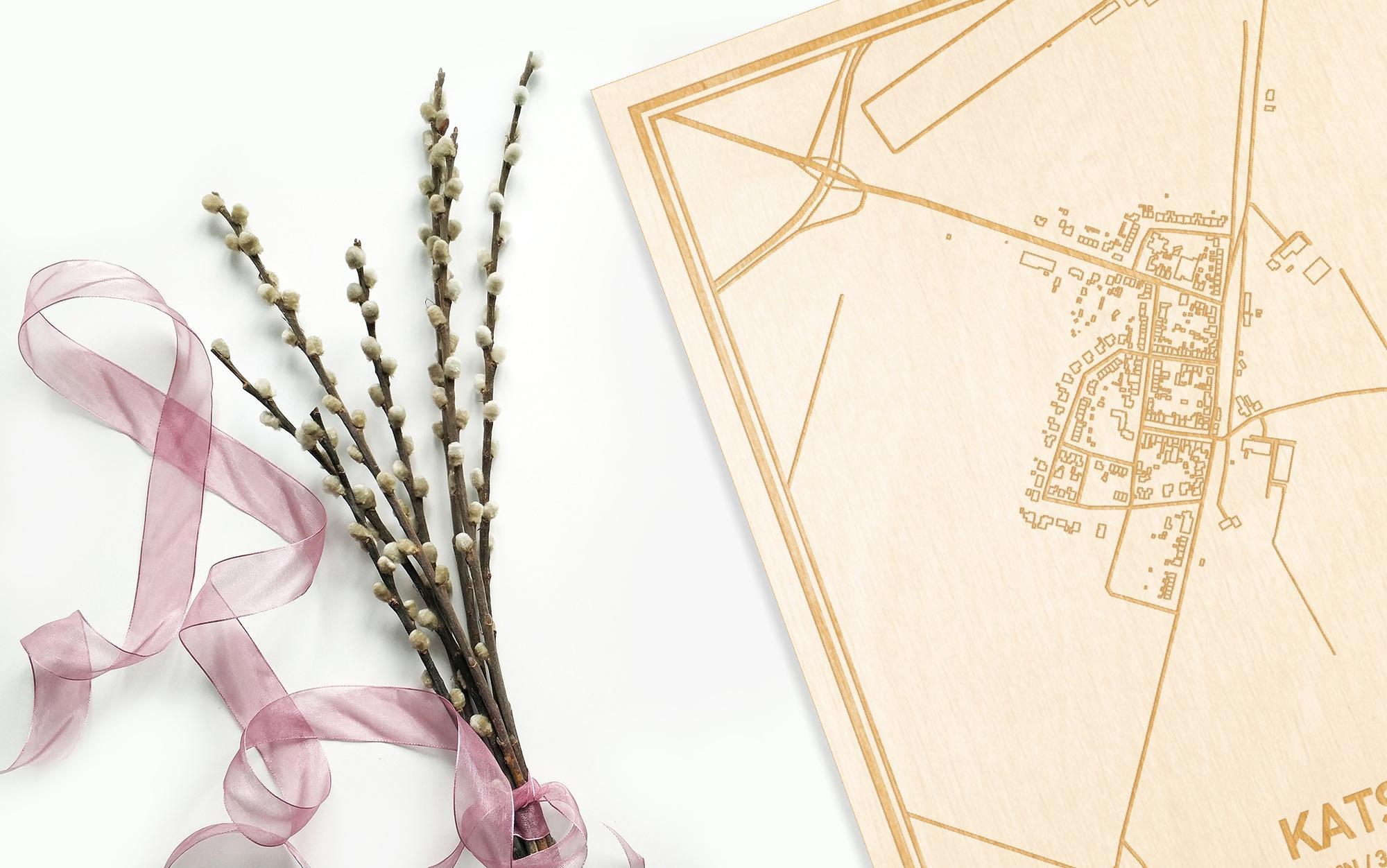 Hier ligt de houten plattegrond Kats naast een bloemetje als gepersonaliseerd cadeau voor haar.