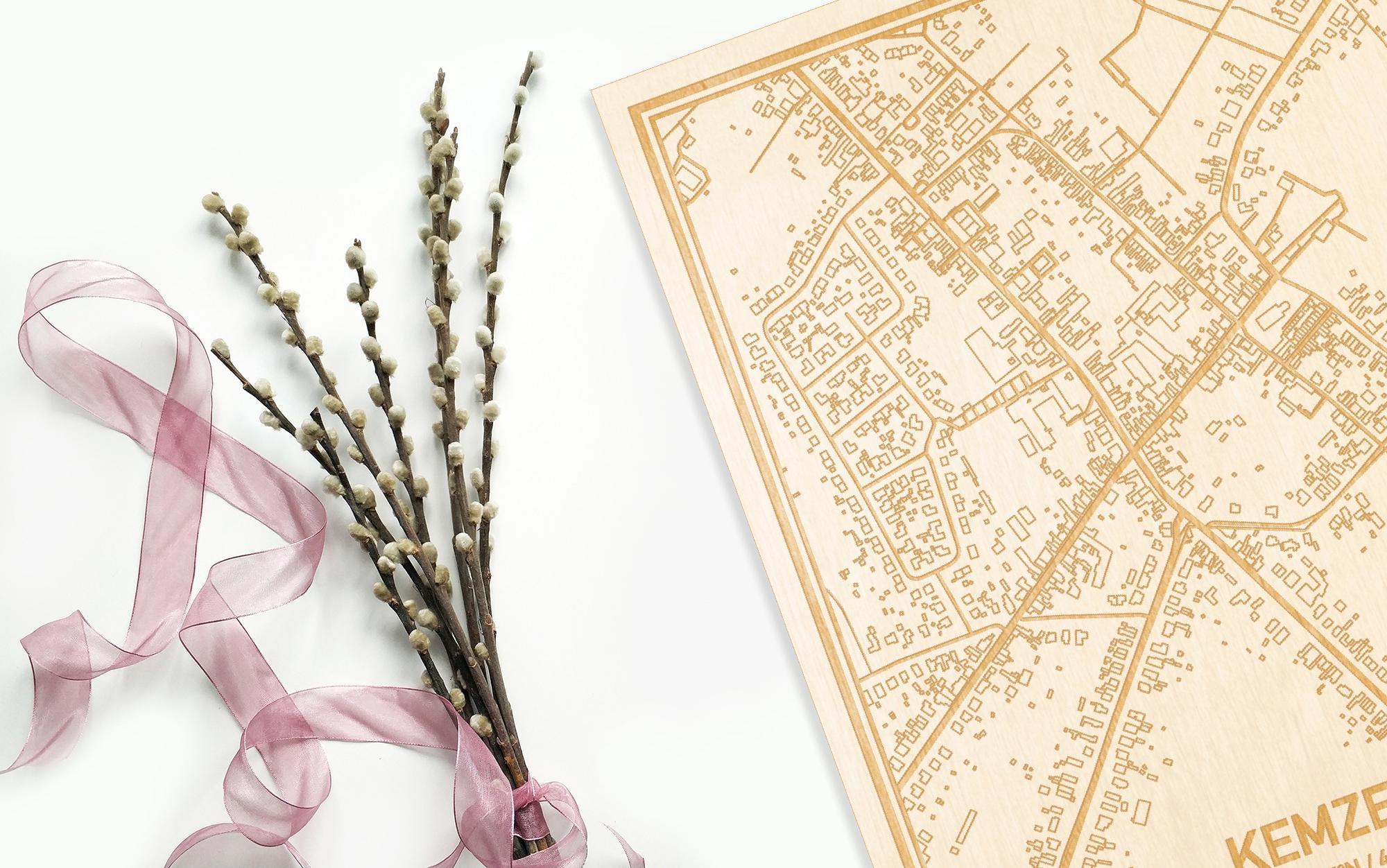 Hier ligt de houten plattegrond Kemzeke naast een bloemetje als gepersonaliseerd cadeau voor haar.