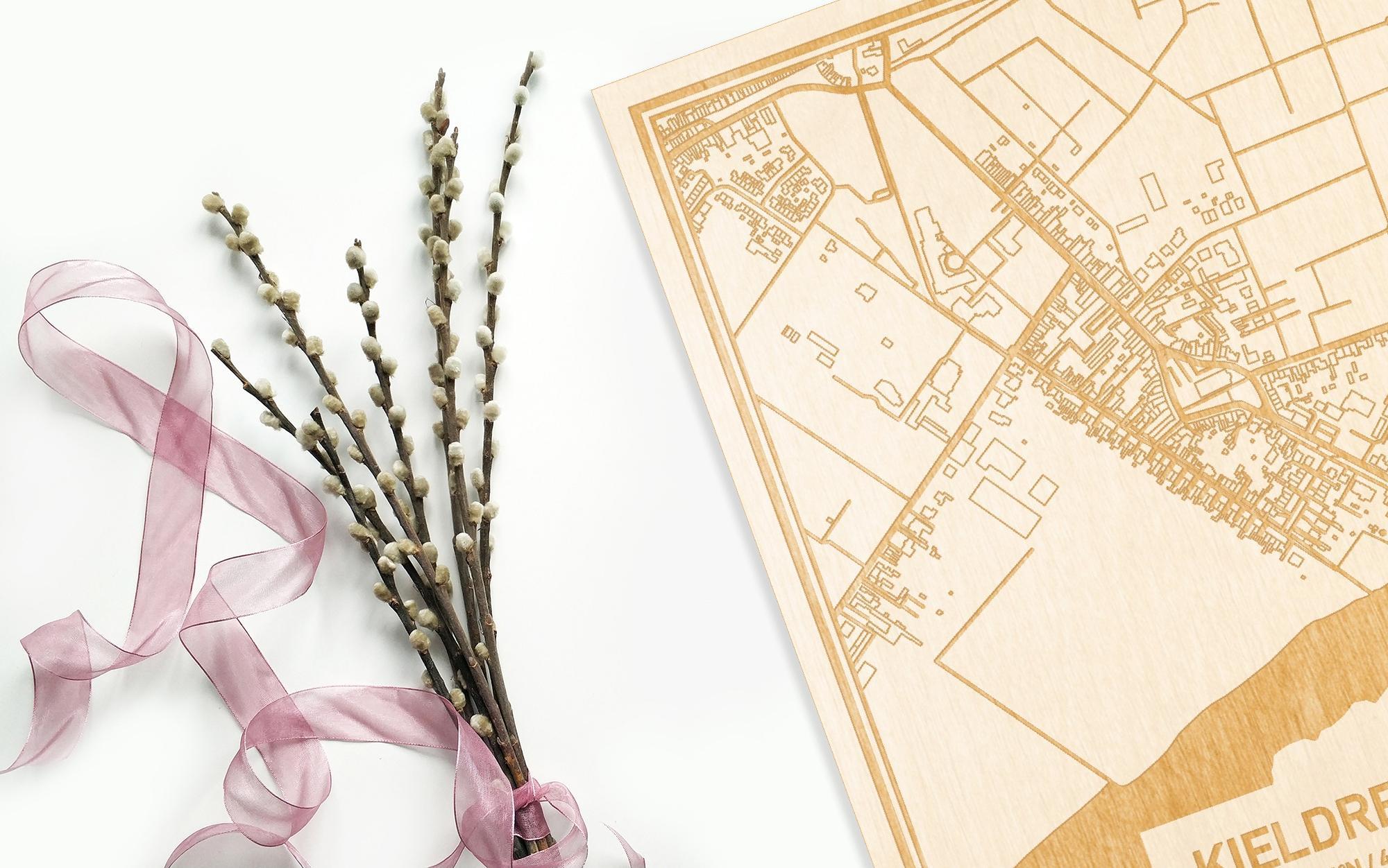 Hier ligt de houten plattegrond Kieldrecht naast een bloemetje als gepersonaliseerd cadeau voor haar.