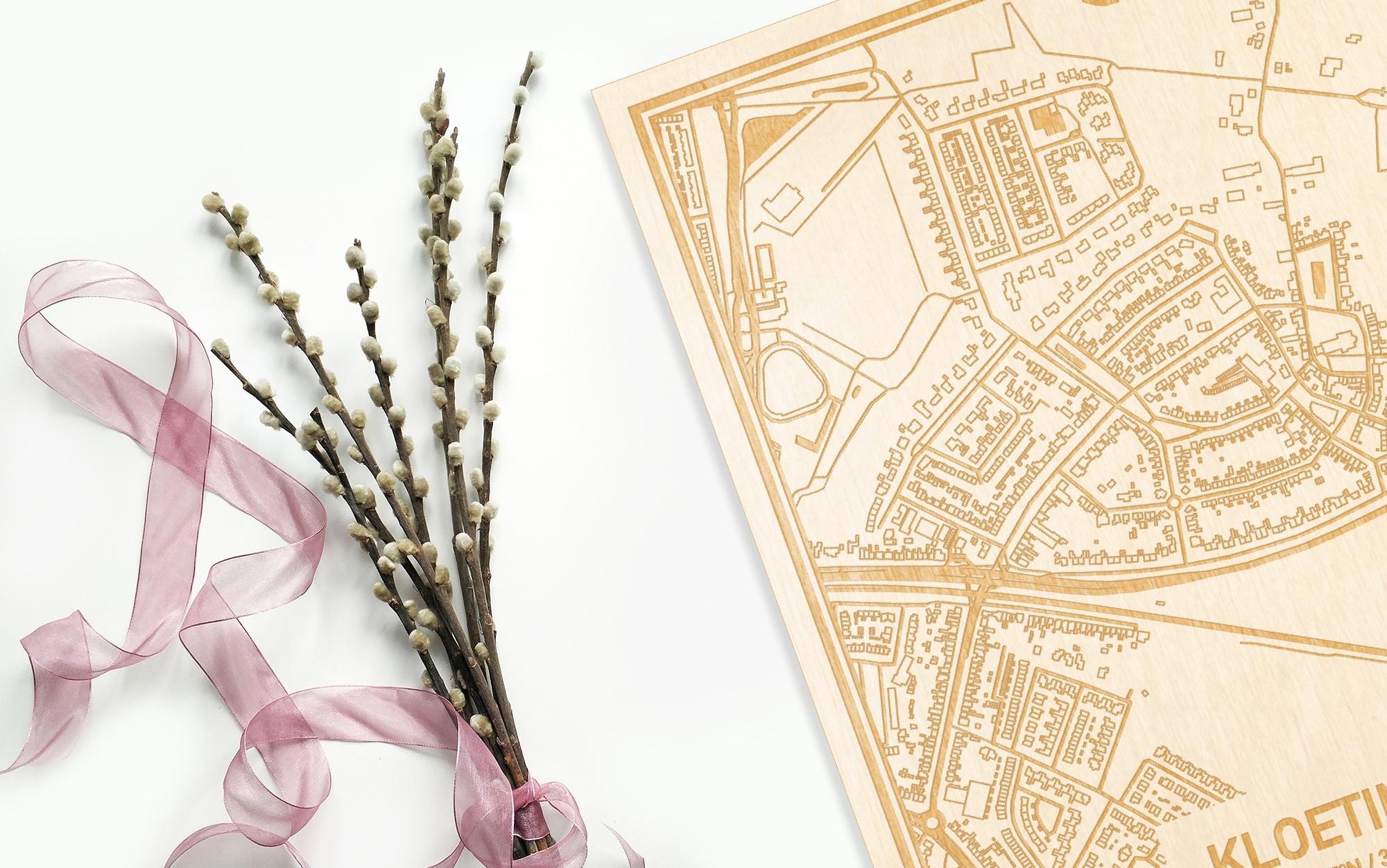 Hier ligt de houten plattegrond Kloetinge naast een bloemetje als gepersonaliseerd cadeau voor haar.
