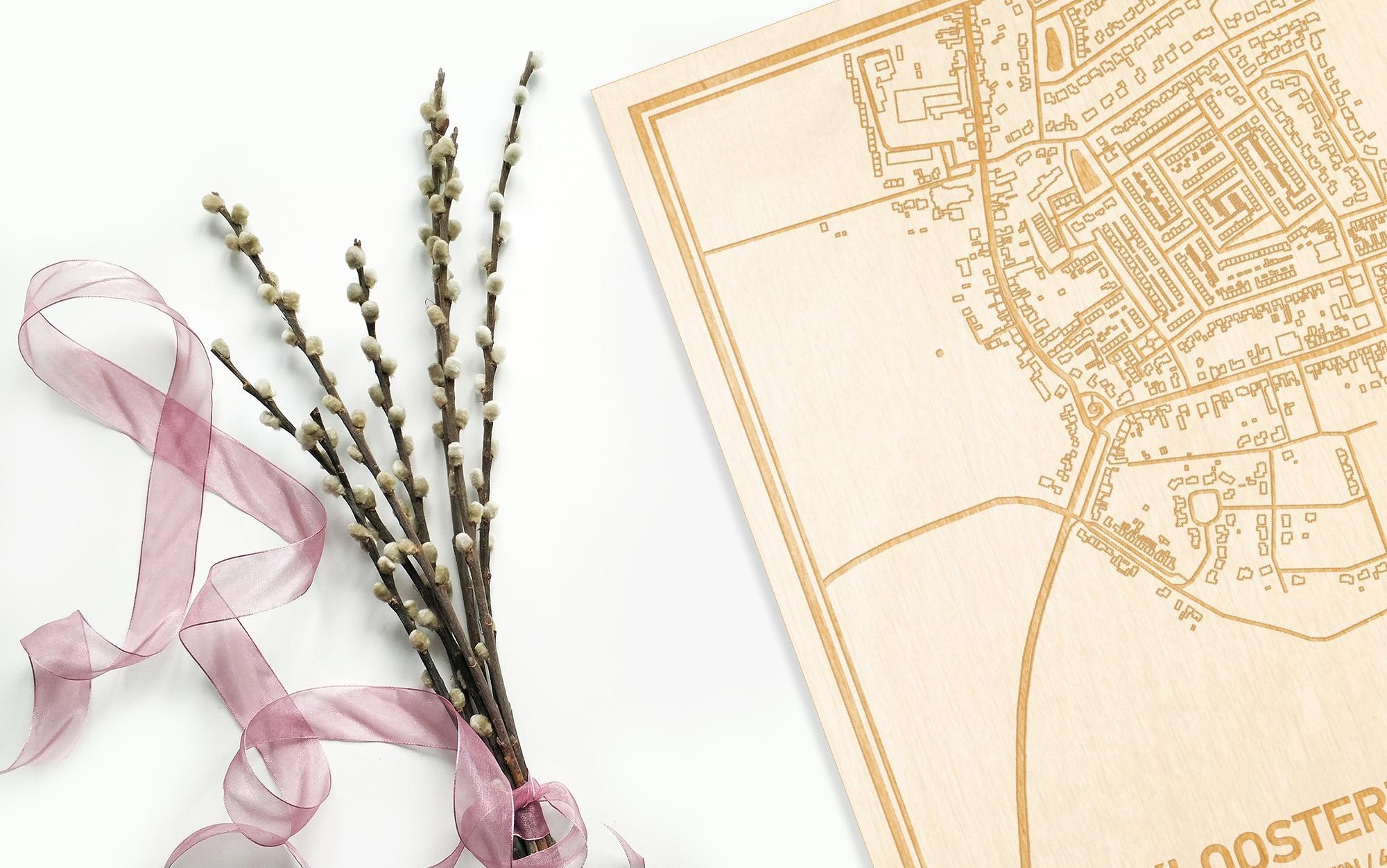 Hier ligt de houten plattegrond Kloosterzande naast een bloemetje als gepersonaliseerd cadeau voor haar.