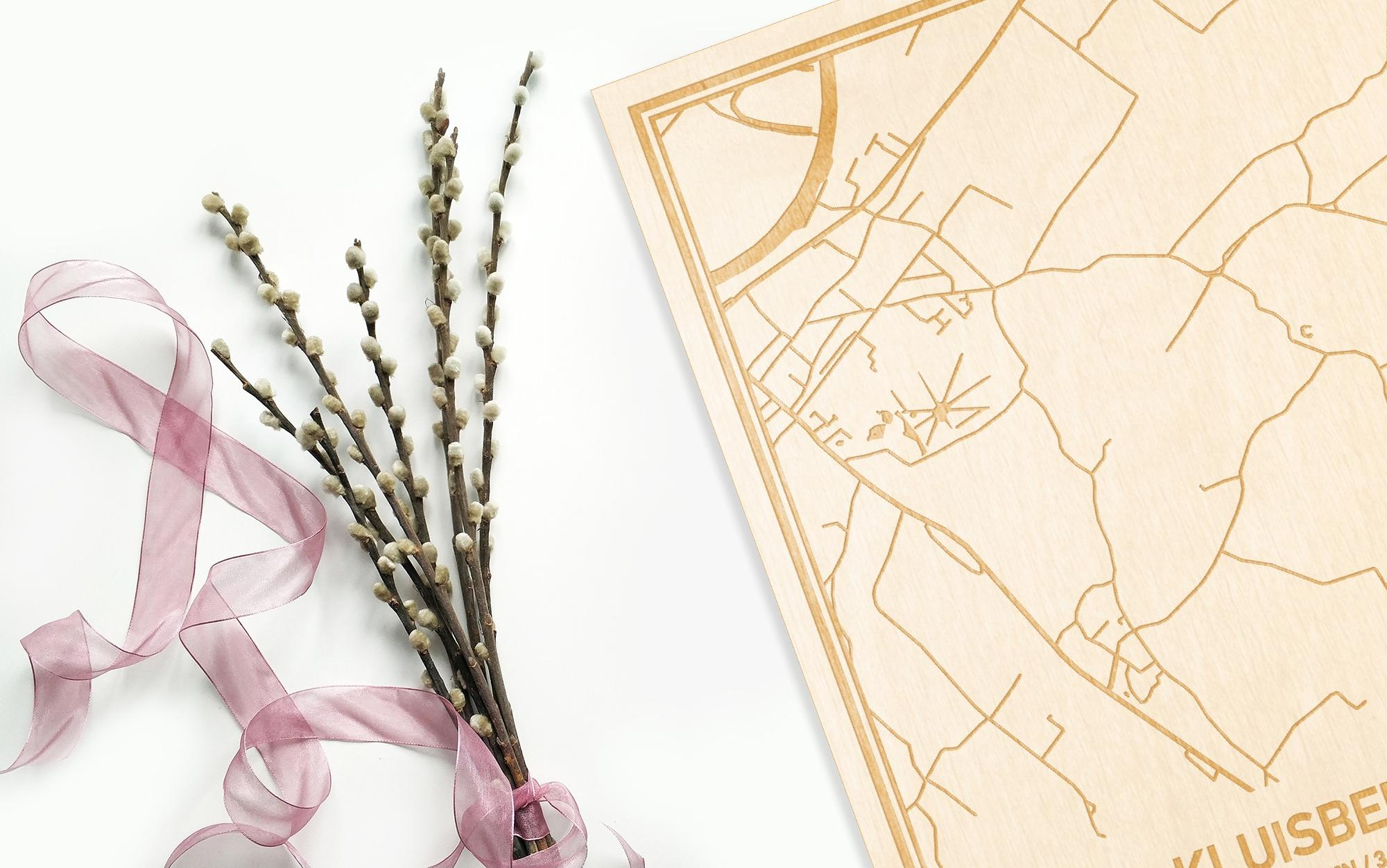 Hier ligt de houten plattegrond Kluisbergen naast een bloemetje als gepersonaliseerd cadeau voor haar.