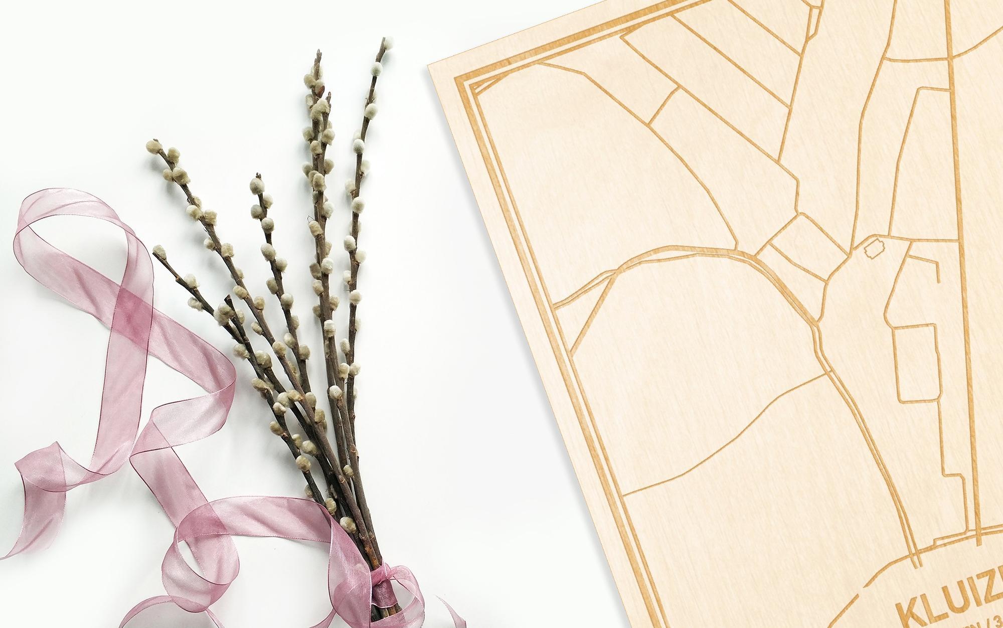 Hier ligt de houten plattegrond Kluizen naast een bloemetje als gepersonaliseerd cadeau voor haar.