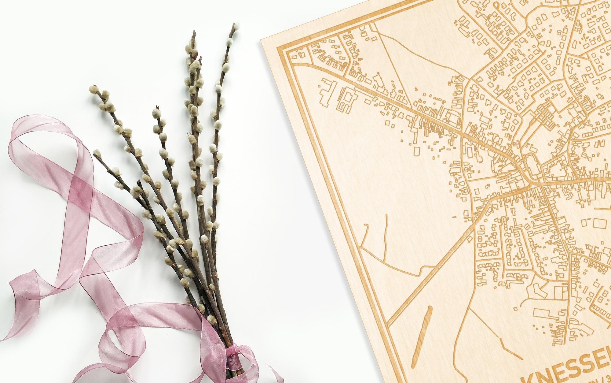 Hier ligt de houten plattegrond Knesselare naast een bloemetje als gepersonaliseerd cadeau voor haar.