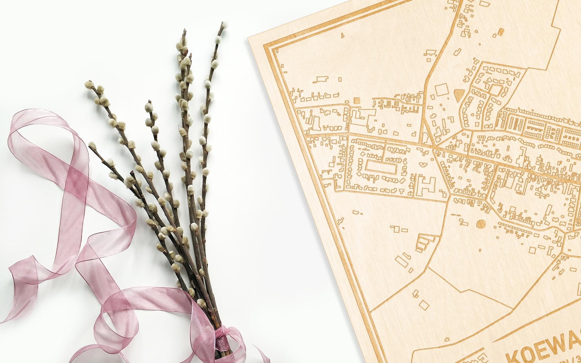Hier ligt de houten plattegrond Koewacht naast een bloemetje als gepersonaliseerd cadeau voor haar.
