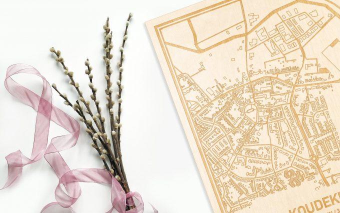 Hier ligt de houten plattegrond Koudekerke naast een bloemetje als gepersonaliseerd cadeau voor haar.