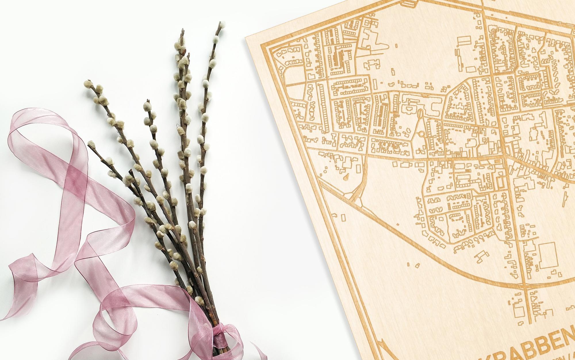 Hier ligt de houten plattegrond Krabbendijke naast een bloemetje als gepersonaliseerd cadeau voor haar.