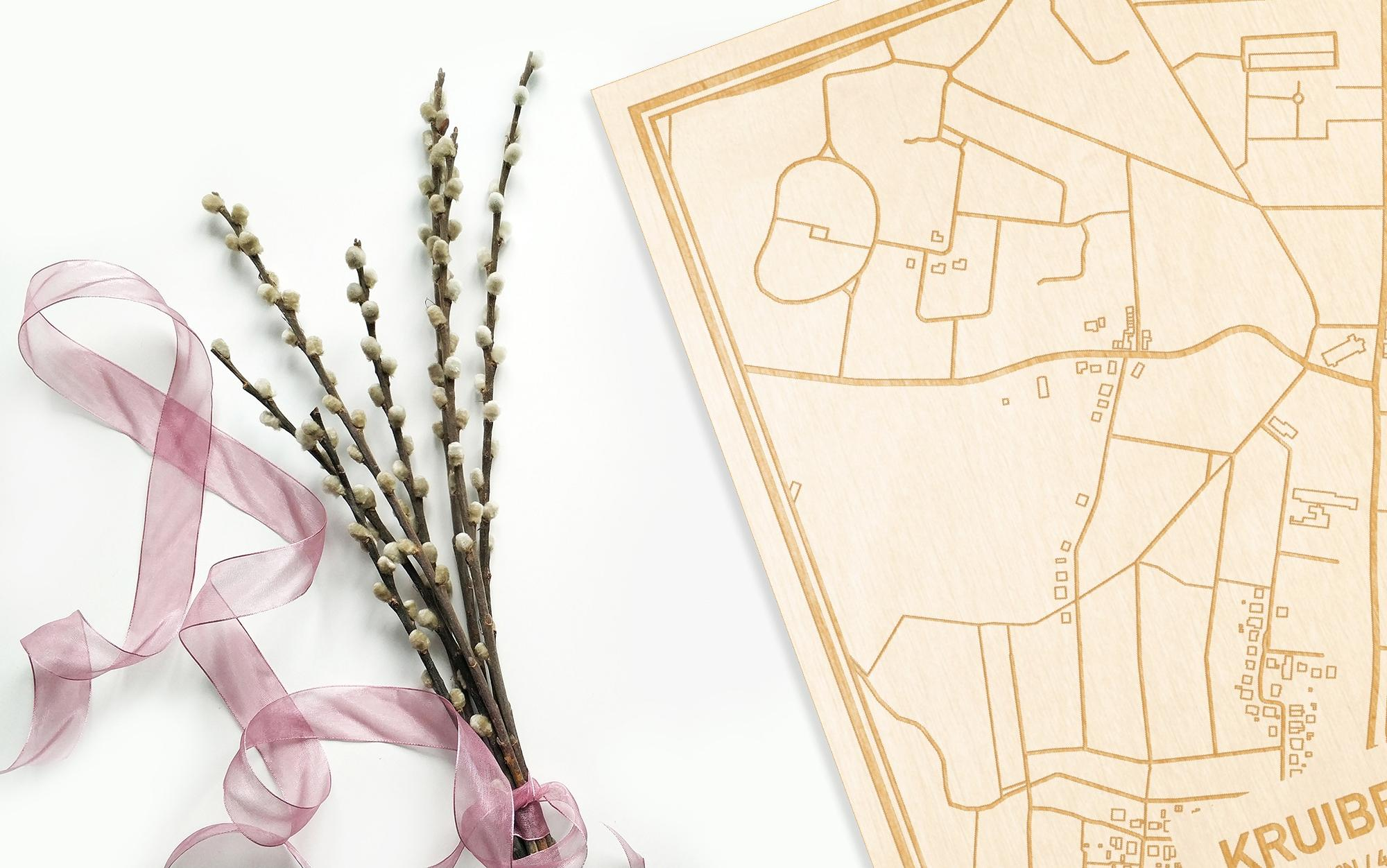 Hier ligt de houten plattegrond Kruibeke naast een bloemetje als gepersonaliseerd cadeau voor haar.