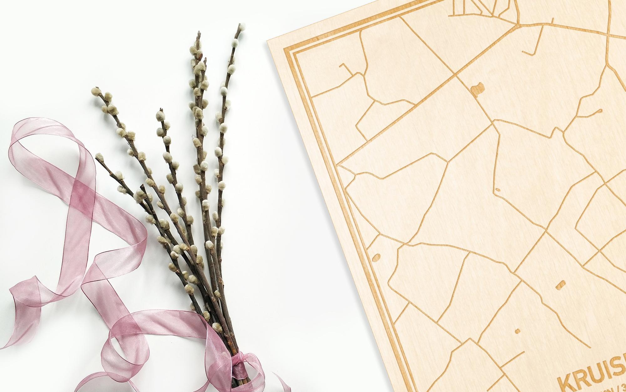 Hier ligt de houten plattegrond Kruisem naast een bloemetje als gepersonaliseerd cadeau voor haar.