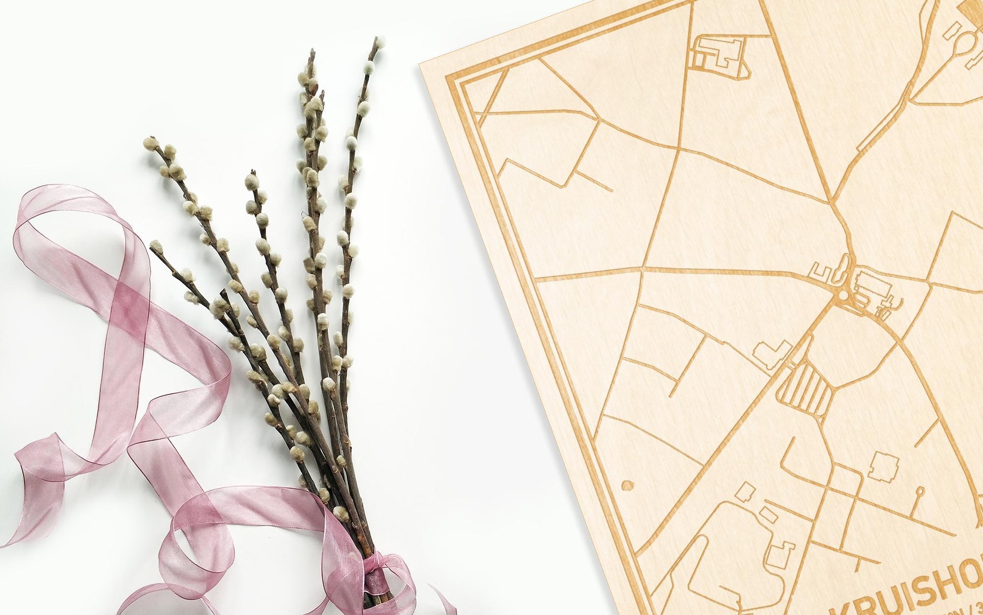 Hier ligt de houten plattegrond Kruishoutem naast een bloemetje als gepersonaliseerd cadeau voor haar.