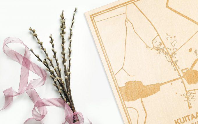 Hier ligt de houten plattegrond Kuitaart naast een bloemetje als gepersonaliseerd cadeau voor haar.