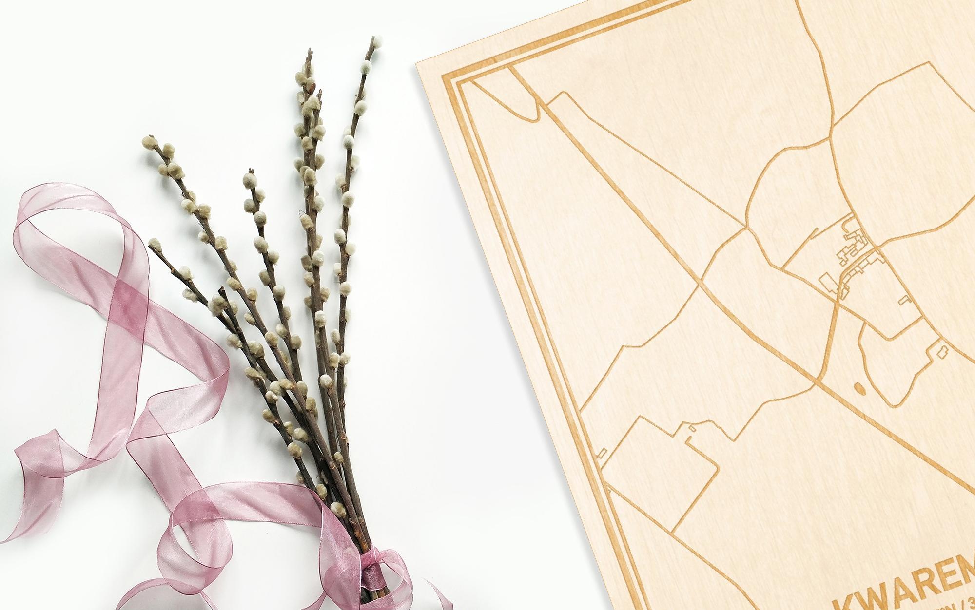 Hier ligt de houten plattegrond Kwaremont naast een bloemetje als gepersonaliseerd cadeau voor haar.