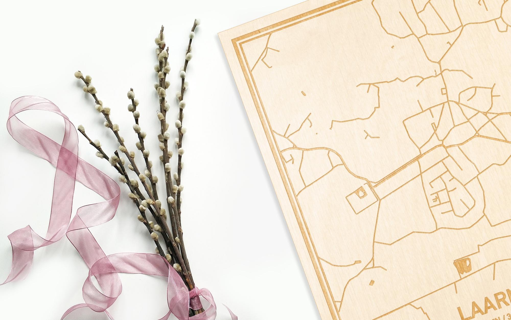 Hier ligt de houten plattegrond Laarne naast een bloemetje als gepersonaliseerd cadeau voor haar.
