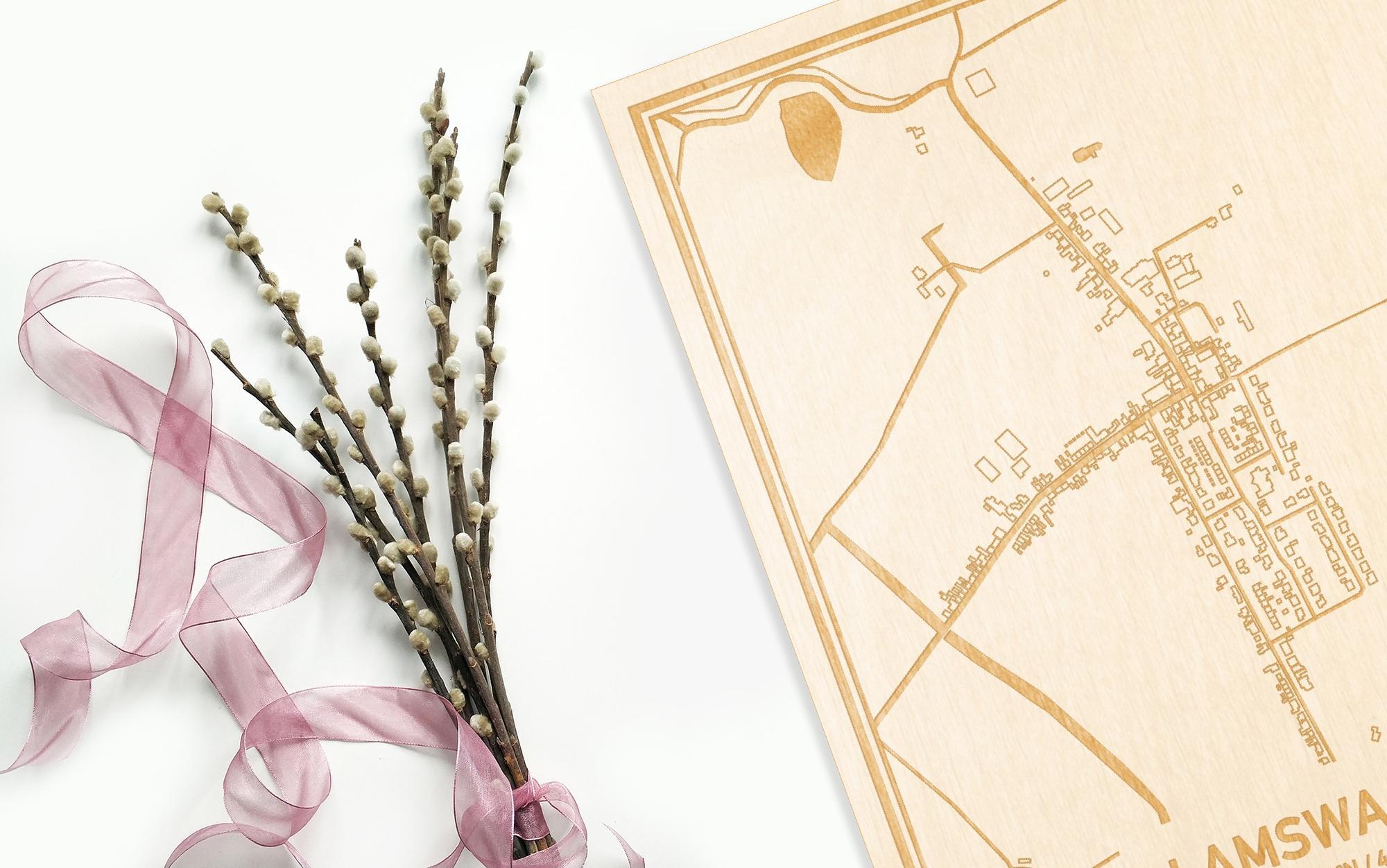 Hier ligt de houten plattegrond Lamswaarde naast een bloemetje als gepersonaliseerd cadeau voor haar.
