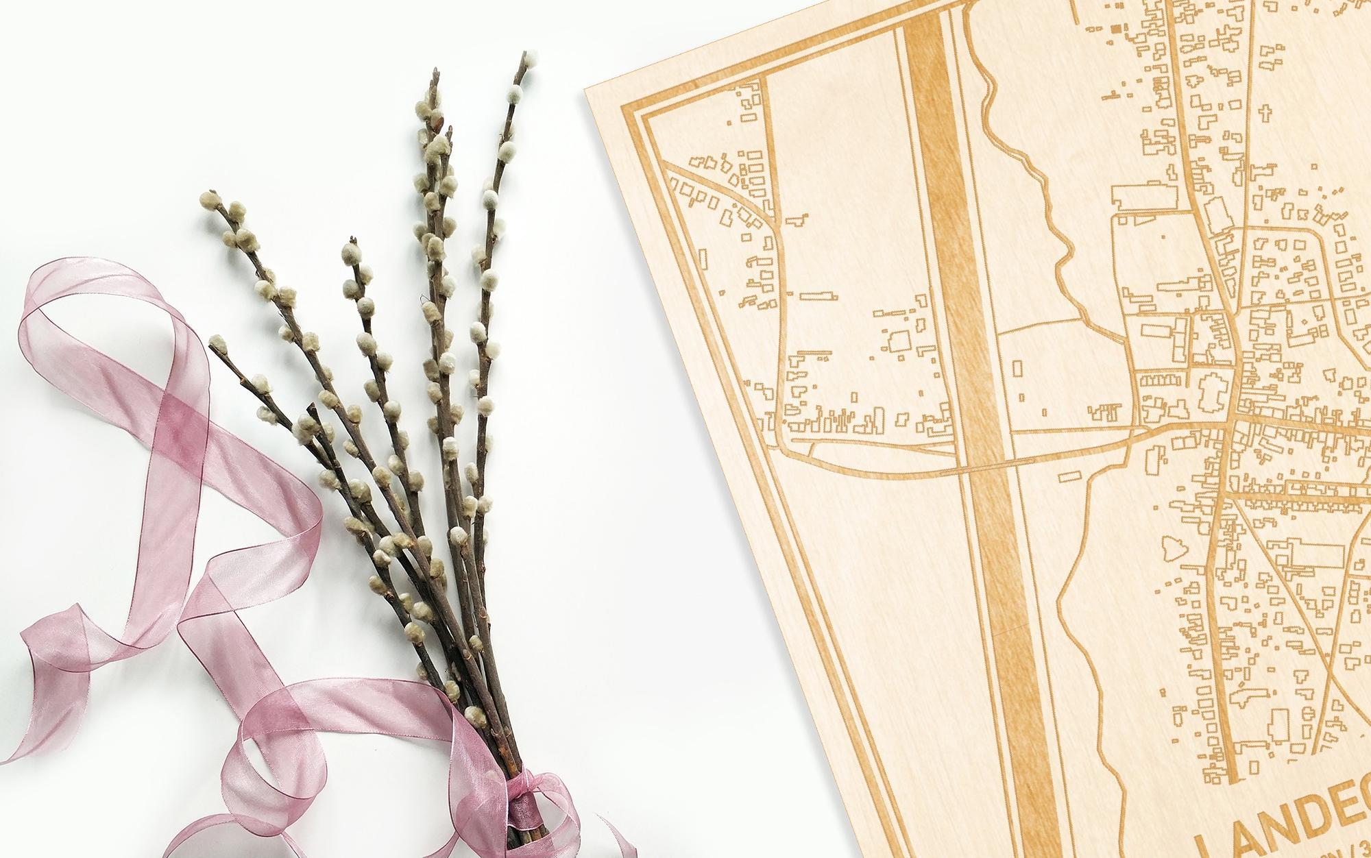 Hier ligt de houten plattegrond Landegem naast een bloemetje als gepersonaliseerd cadeau voor haar.