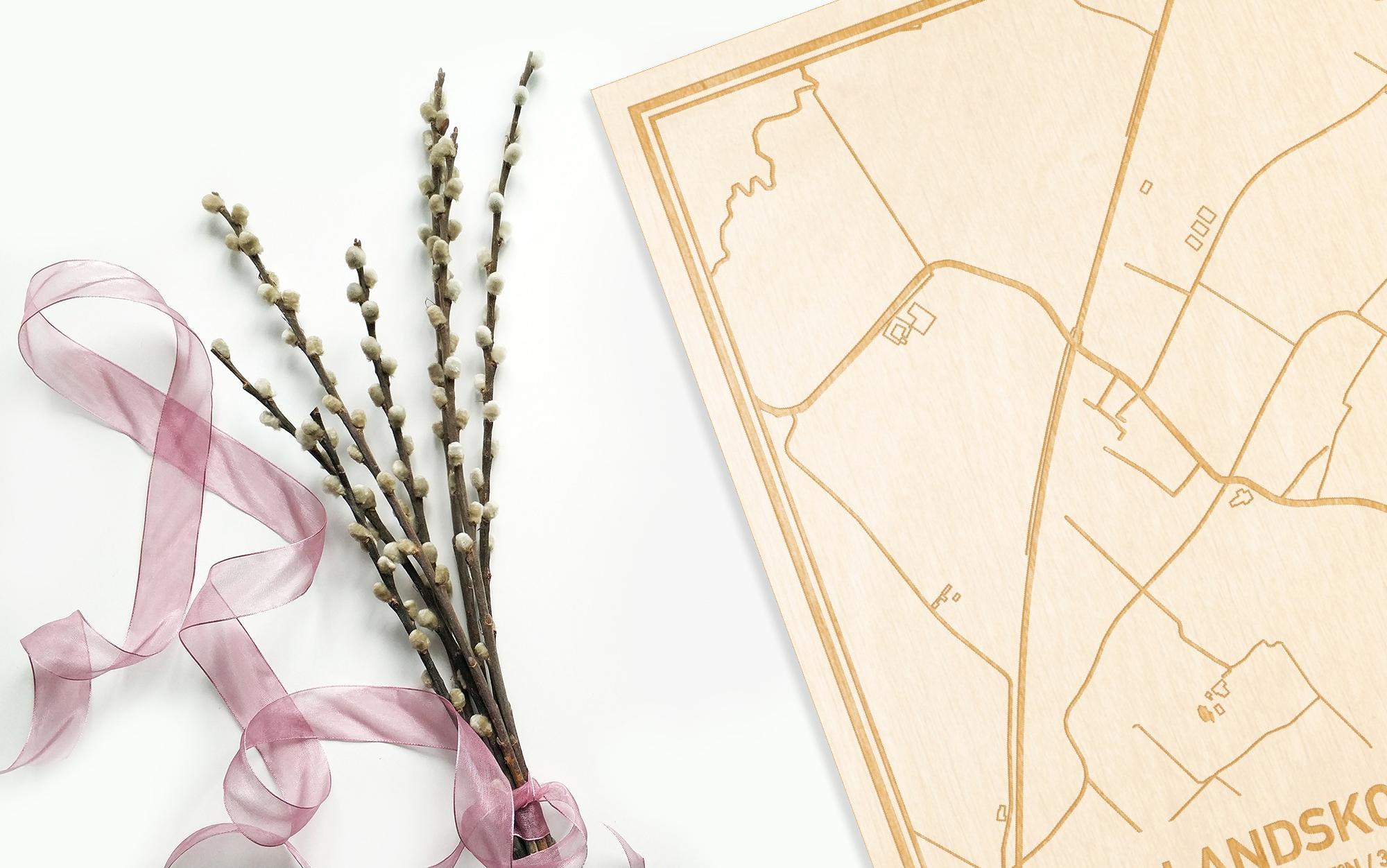 Hier ligt de houten plattegrond Landskouter naast een bloemetje als gepersonaliseerd cadeau voor haar.