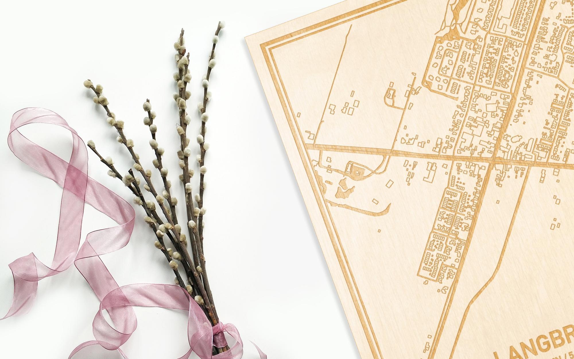 Hier ligt de houten plattegrond Langbroek naast een bloemetje als gepersonaliseerd cadeau voor haar.