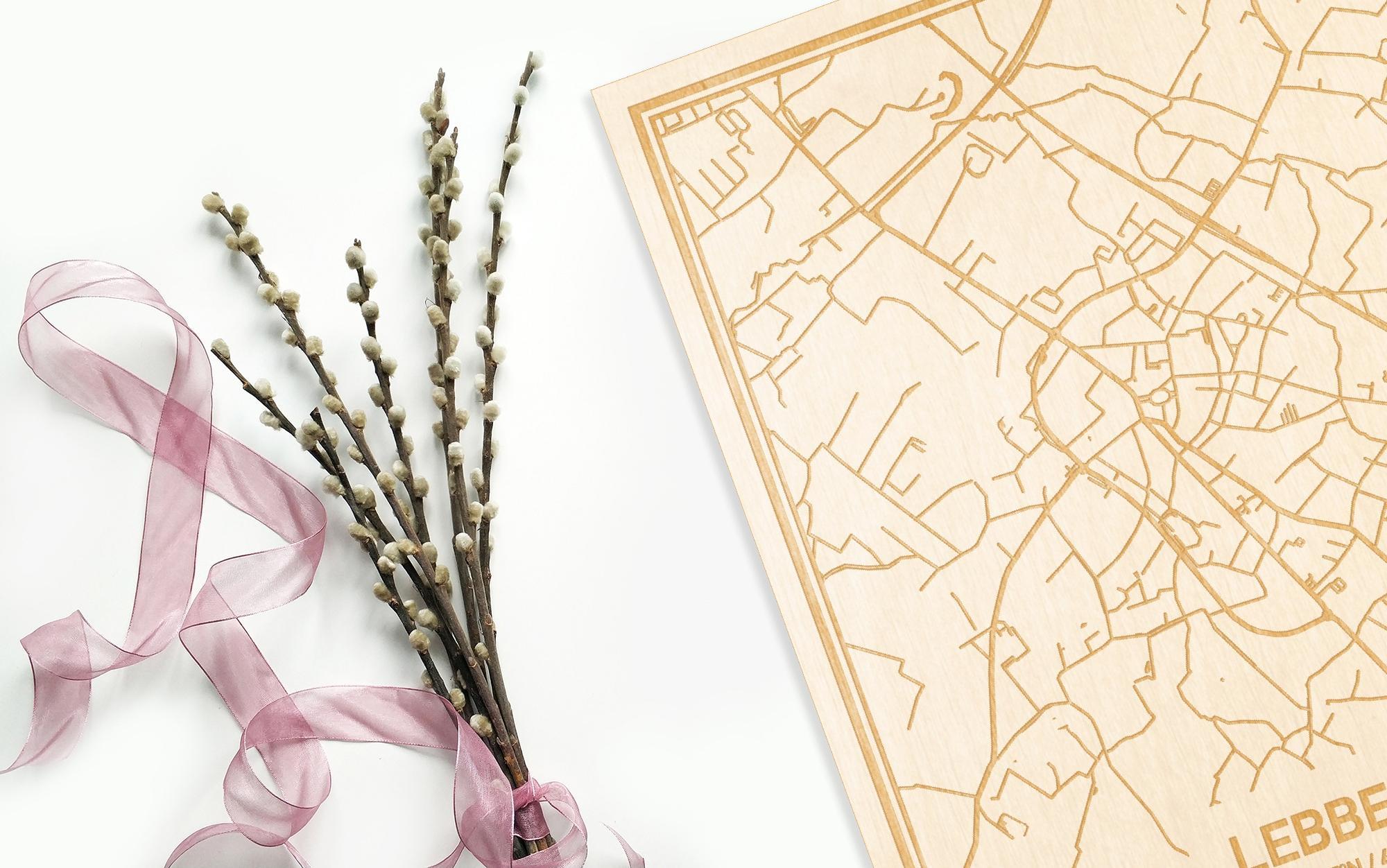 Hier ligt de houten plattegrond Lebbeke naast een bloemetje als gepersonaliseerd cadeau voor haar.