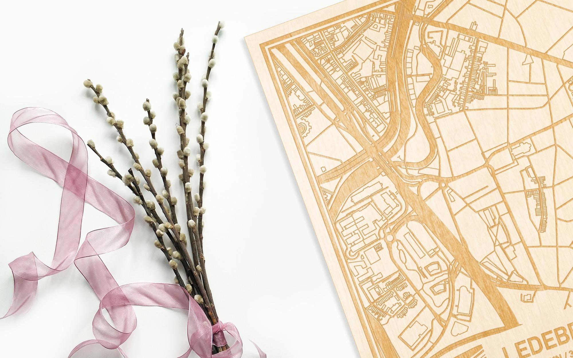 Hier ligt de houten plattegrond Ledeberg naast een bloemetje als gepersonaliseerd cadeau voor haar.