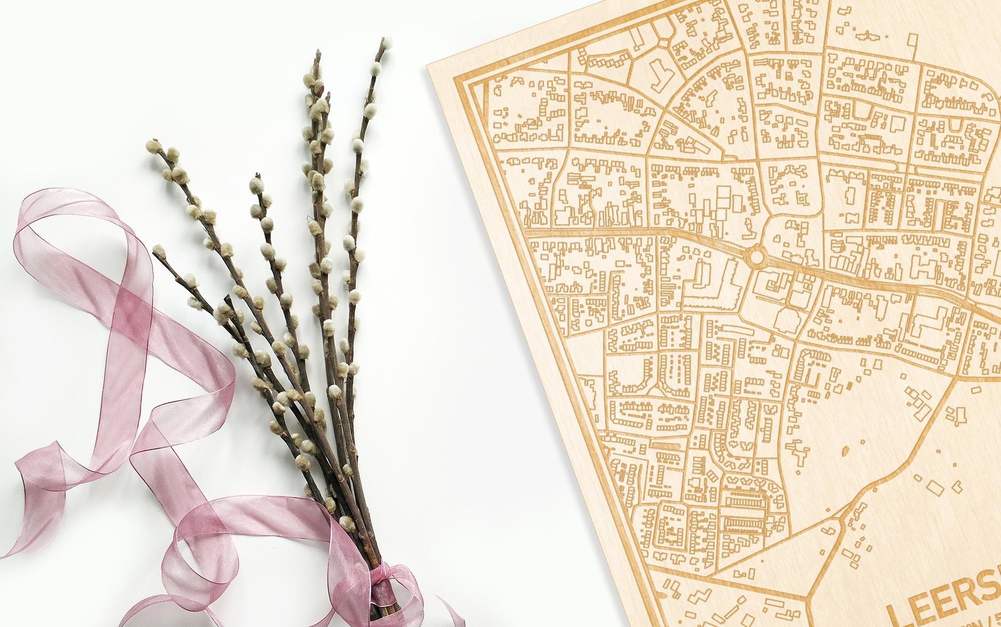 Hier ligt de houten plattegrond Leersum naast een bloemetje als gepersonaliseerd cadeau voor haar.