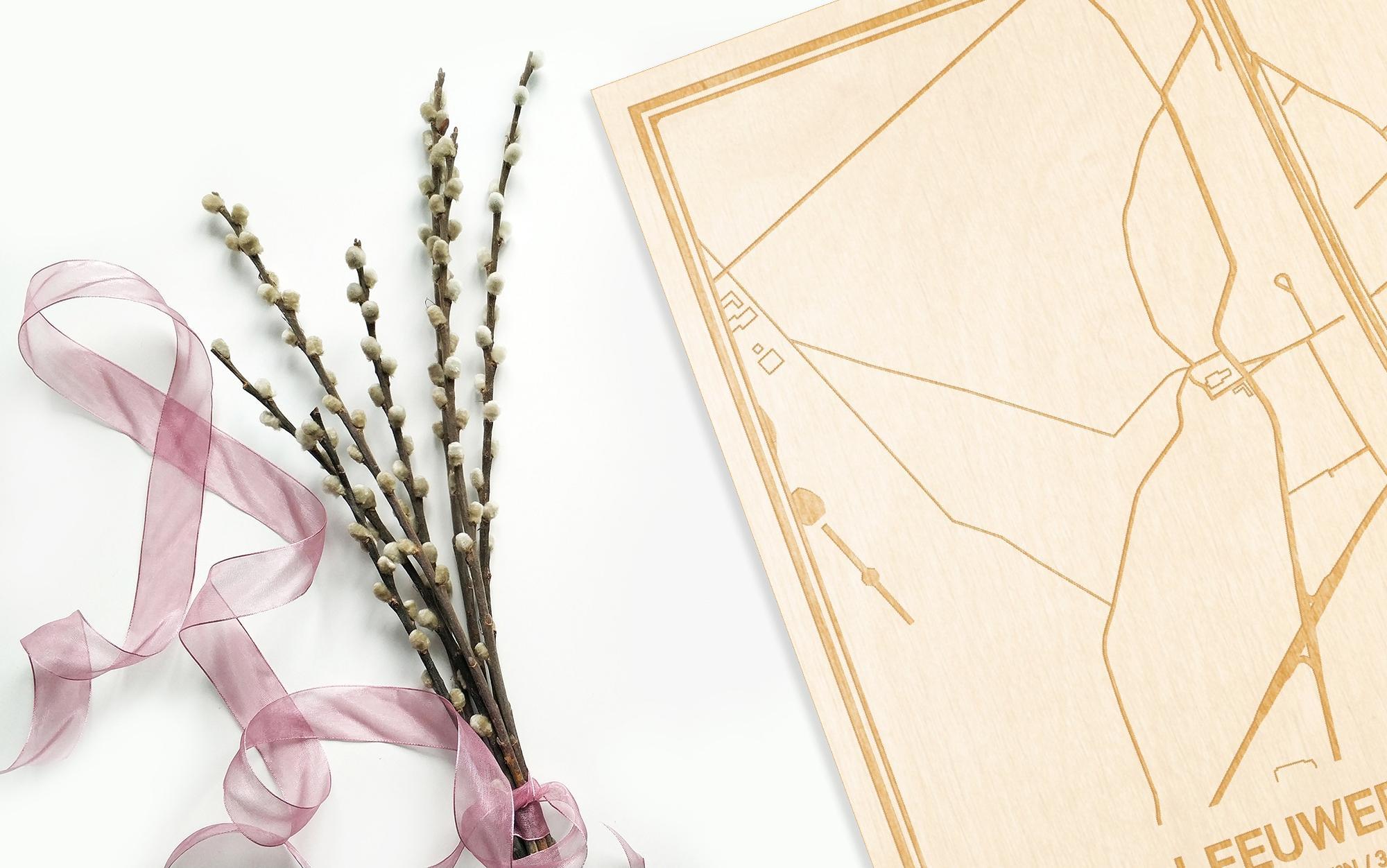Hier ligt de houten plattegrond Leeuwergem naast een bloemetje als gepersonaliseerd cadeau voor haar.