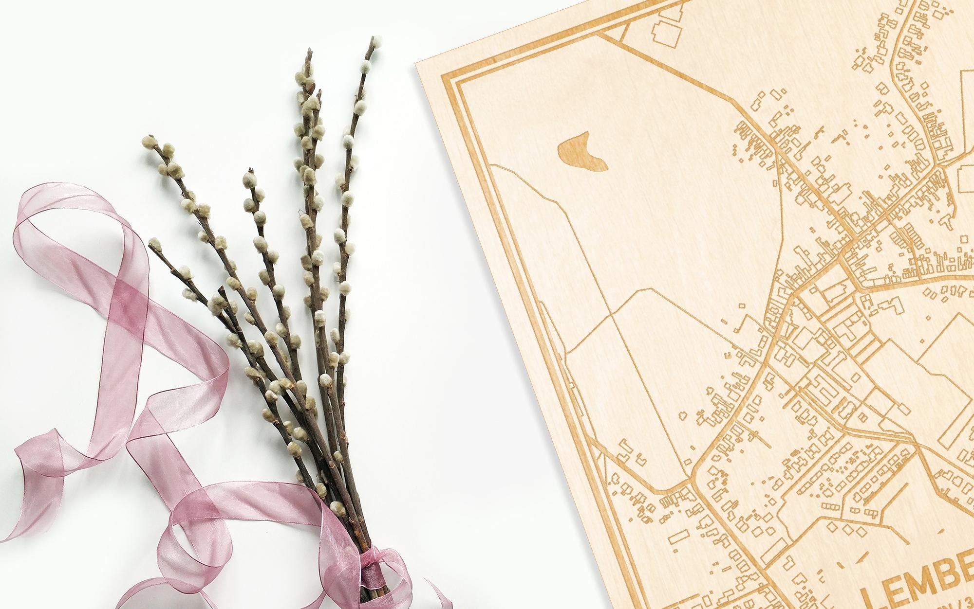 Hier ligt de houten plattegrond Lembeke naast een bloemetje als gepersonaliseerd cadeau voor haar.