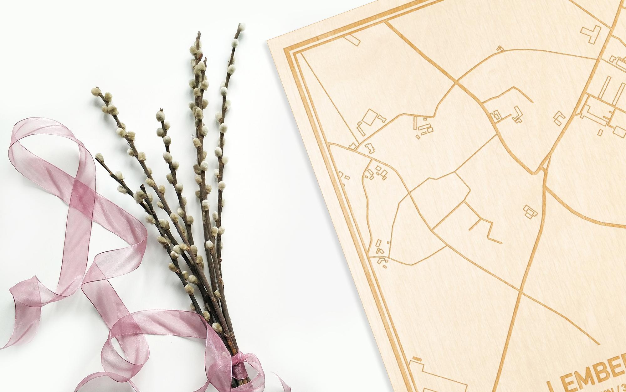 Hier ligt de houten plattegrond Lemberge naast een bloemetje als gepersonaliseerd cadeau voor haar.