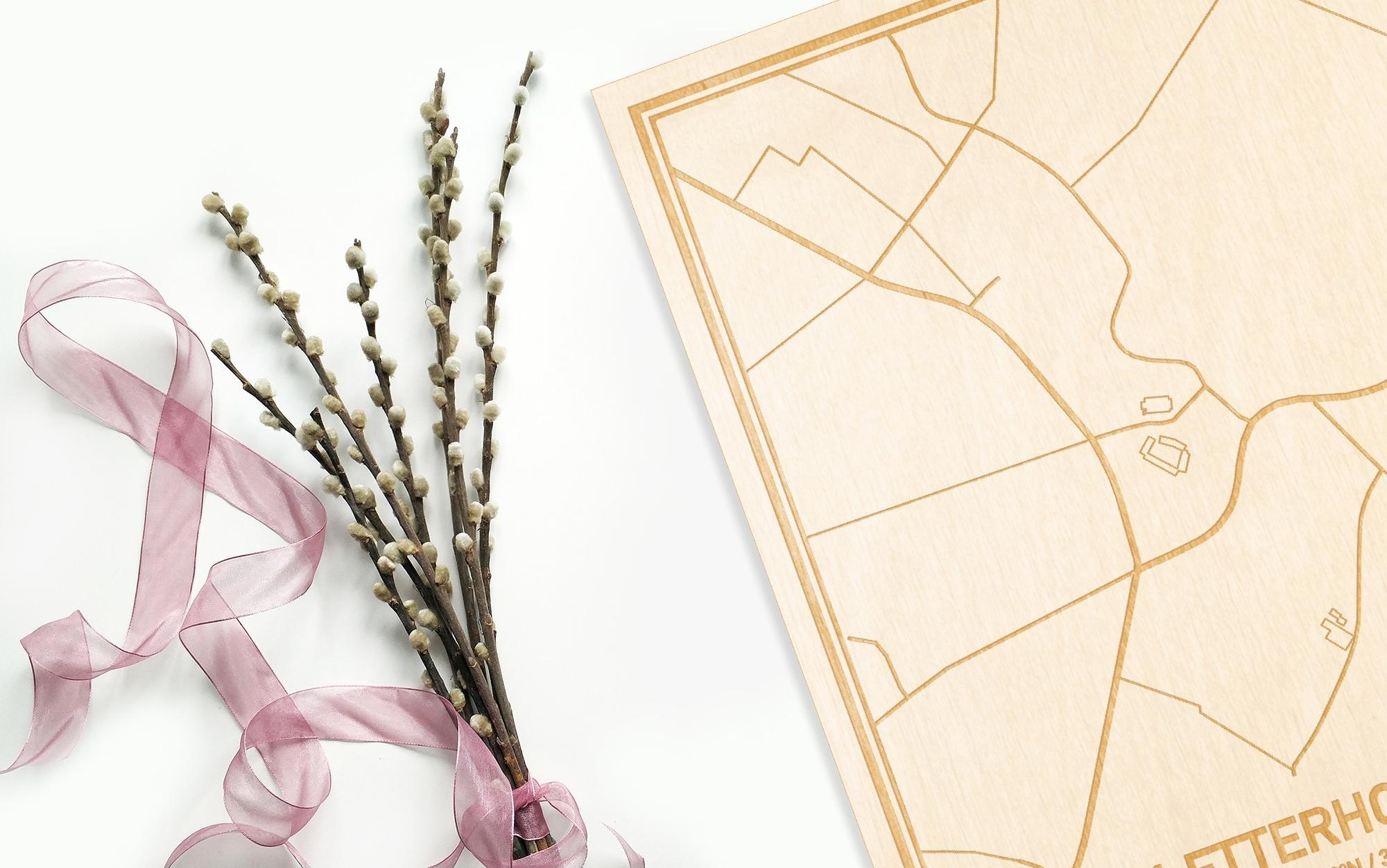 Hier ligt de houten plattegrond Letterhoutem naast een bloemetje als gepersonaliseerd cadeau voor haar.