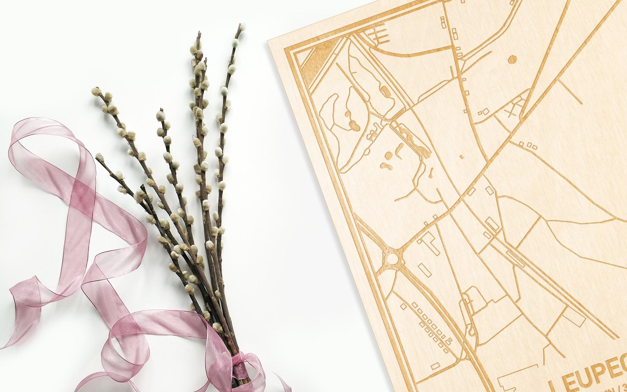 Hier ligt de houten plattegrond Leupegem naast een bloemetje als gepersonaliseerd cadeau voor haar.