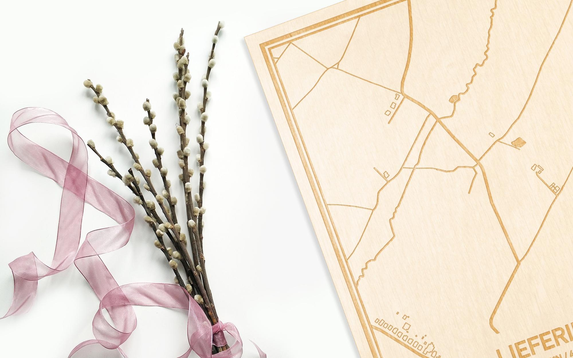 Hier ligt de houten plattegrond Lieferinge naast een bloemetje als gepersonaliseerd cadeau voor haar.