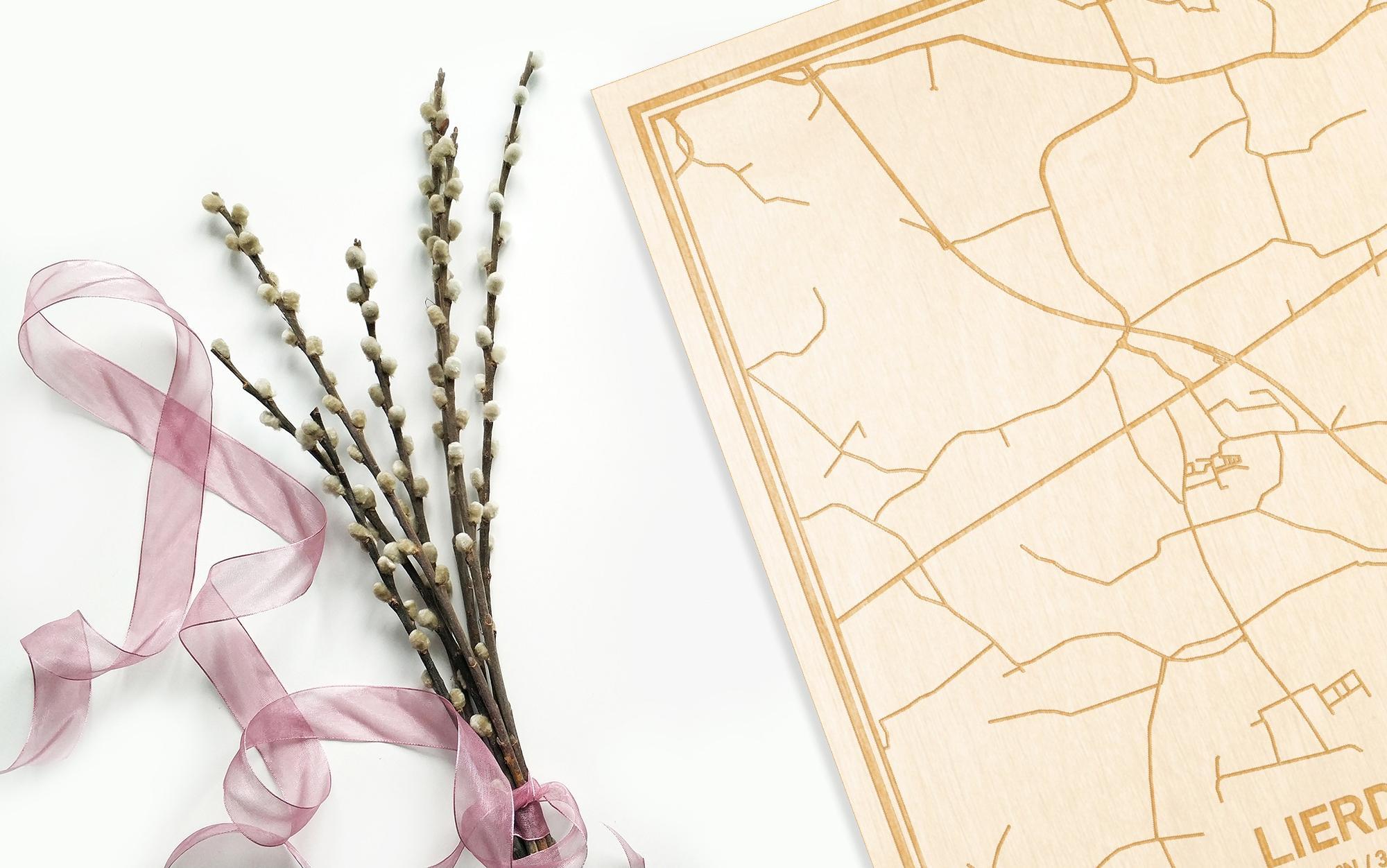 Hier ligt de houten plattegrond Lierde naast een bloemetje als gepersonaliseerd cadeau voor haar.