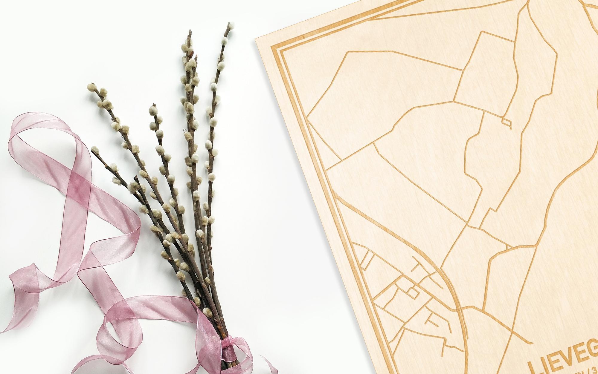 Hier ligt de houten plattegrond Lievegem naast een bloemetje als gepersonaliseerd cadeau voor haar.