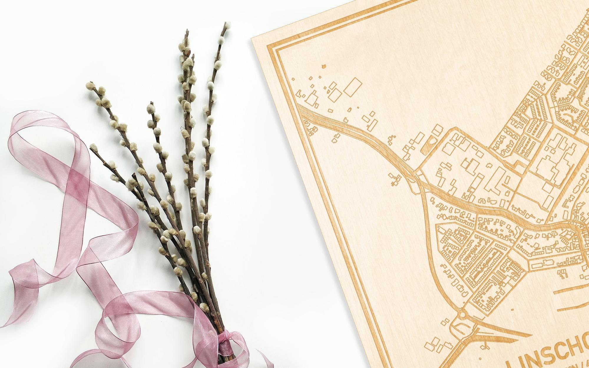 Hier ligt de houten plattegrond Linschoten naast een bloemetje als gepersonaliseerd cadeau voor haar.