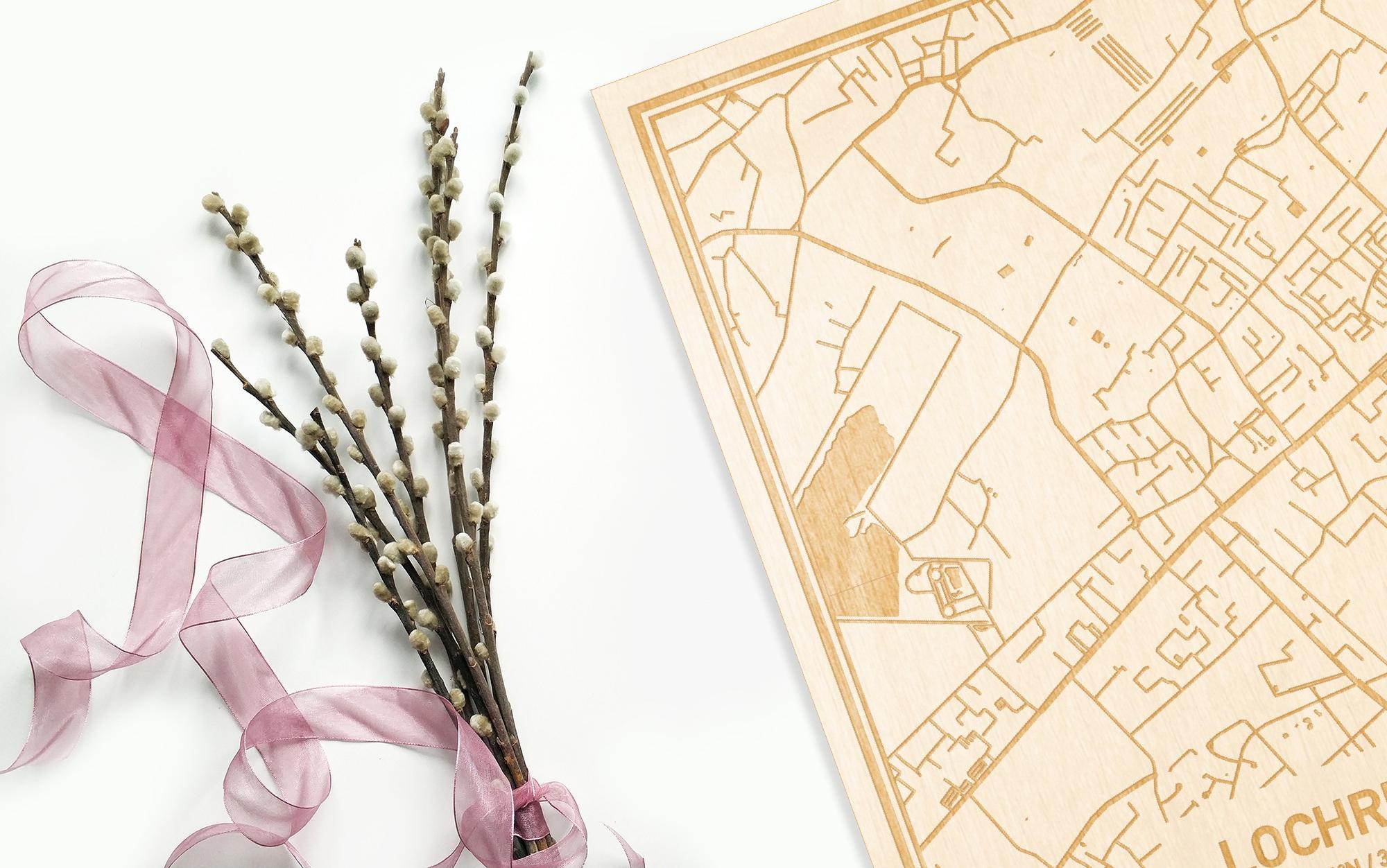 Hier ligt de houten plattegrond Lochristi naast een bloemetje als gepersonaliseerd cadeau voor haar.