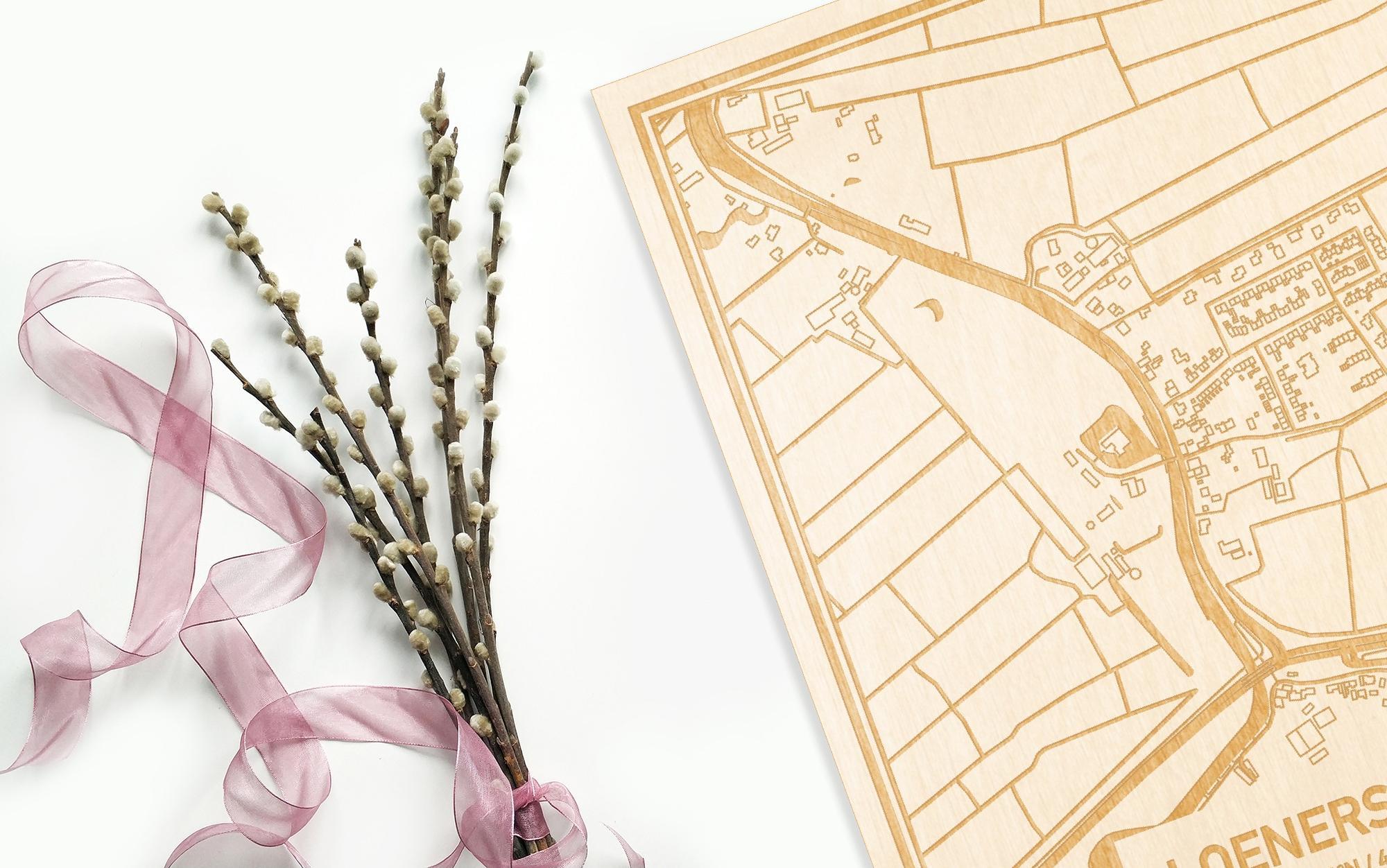Hier ligt de houten plattegrond Loenersloot naast een bloemetje als gepersonaliseerd cadeau voor haar.