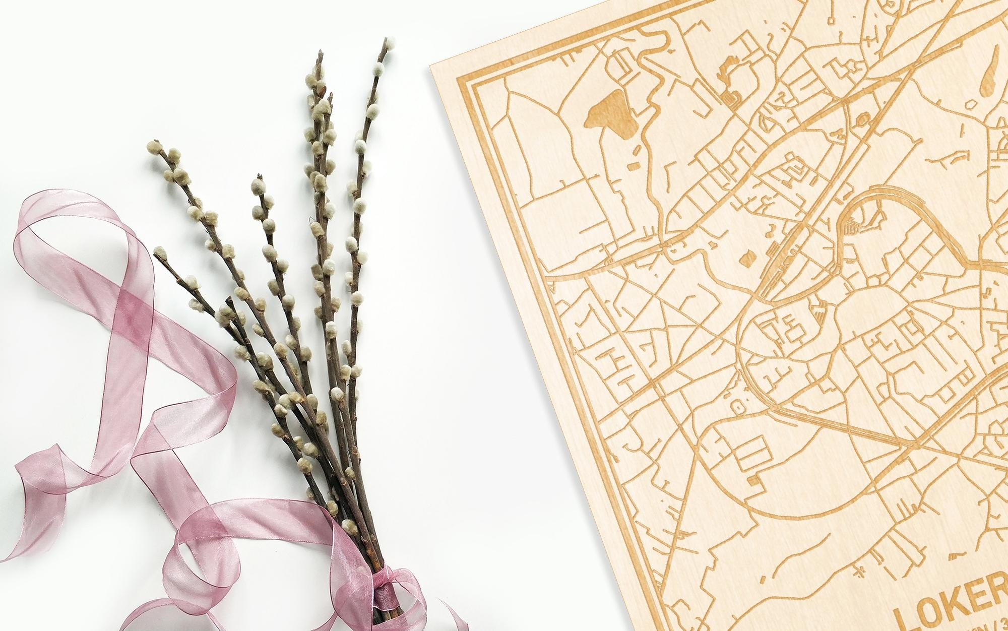 Hier ligt de houten plattegrond Lokeren naast een bloemetje als gepersonaliseerd cadeau voor haar.