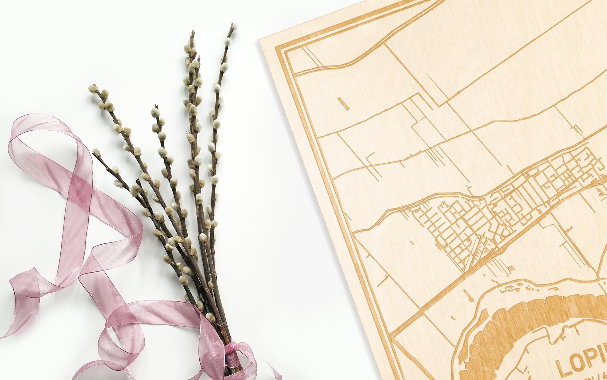Hier ligt de houten plattegrond Lopik naast een bloemetje als gepersonaliseerd cadeau voor haar.
