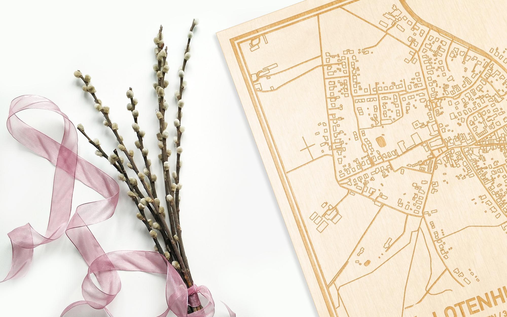 Hier ligt de houten plattegrond Lotenhulle naast een bloemetje als gepersonaliseerd cadeau voor haar.