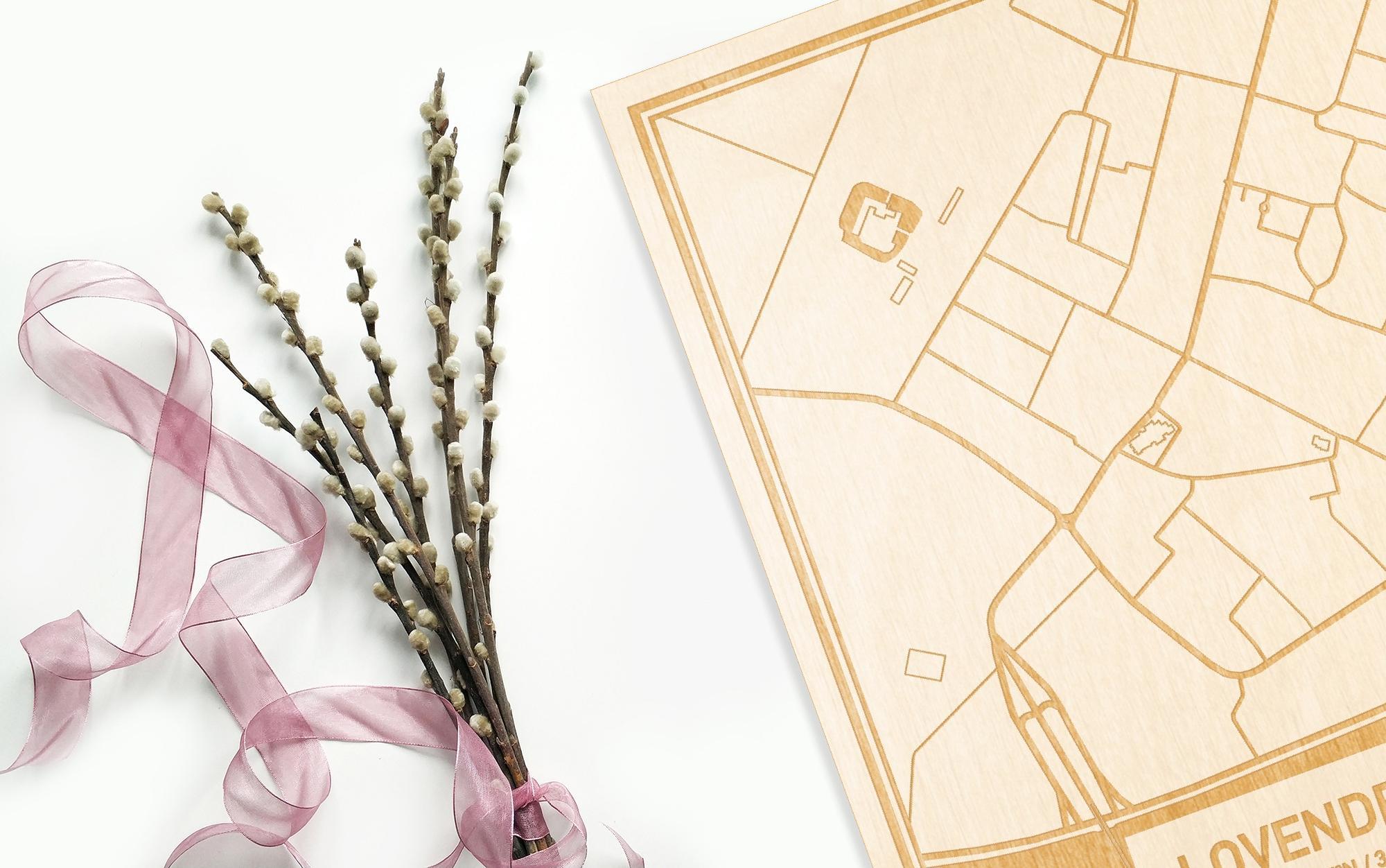 Hier ligt de houten plattegrond Lovendegem naast een bloemetje als gepersonaliseerd cadeau voor haar.