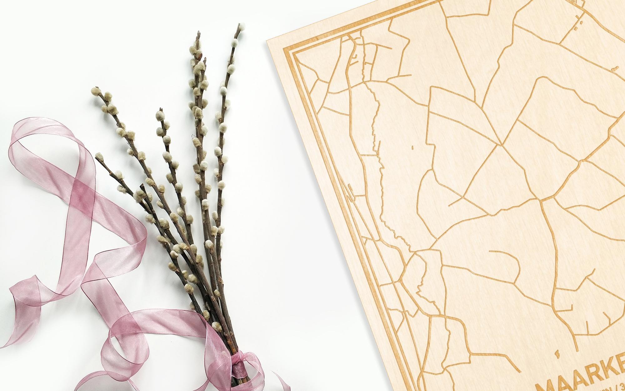 Hier ligt de houten plattegrond Maarkedal naast een bloemetje als gepersonaliseerd cadeau voor haar.
