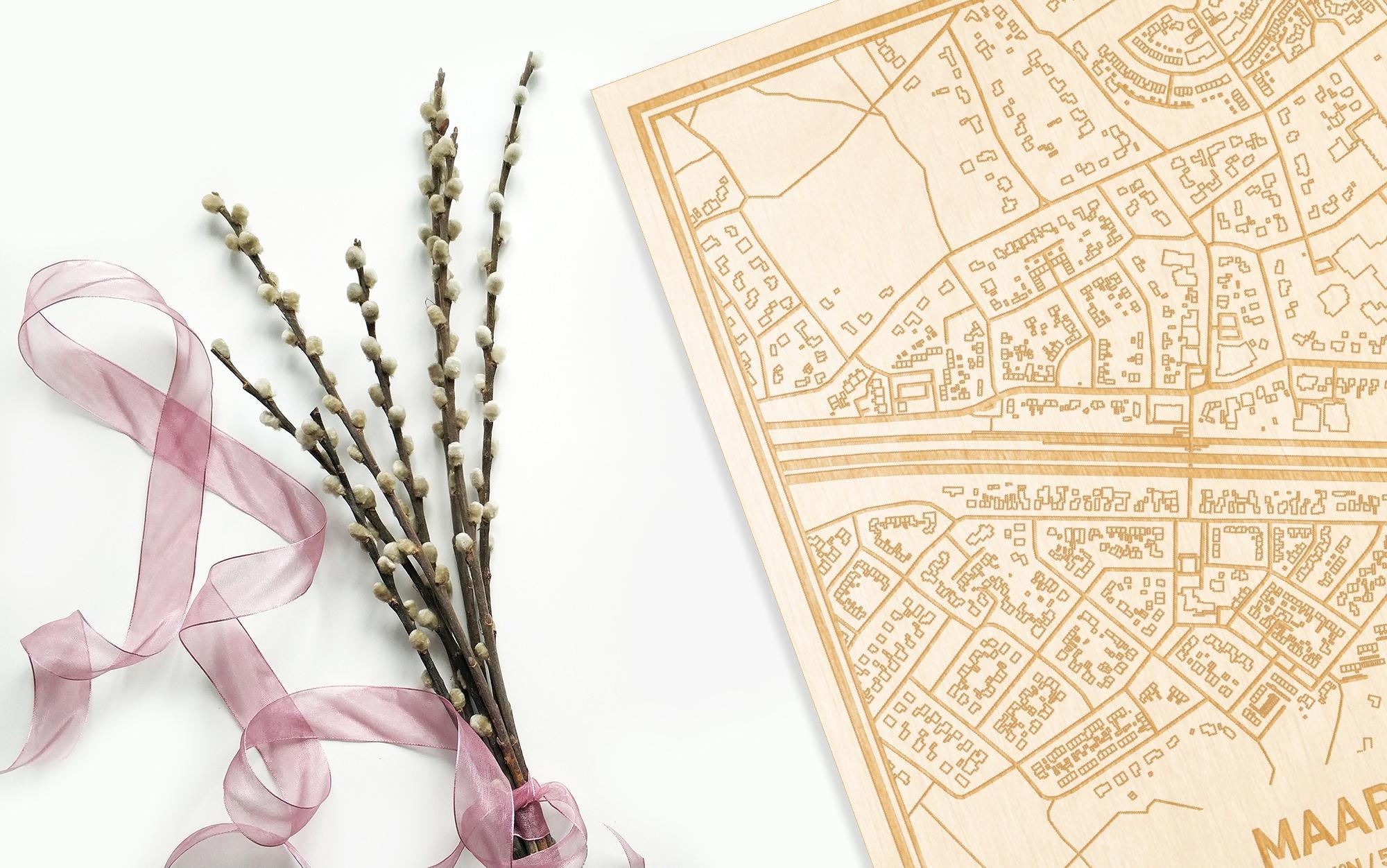 Hier ligt de houten plattegrond Maarn naast een bloemetje als gepersonaliseerd cadeau voor haar.