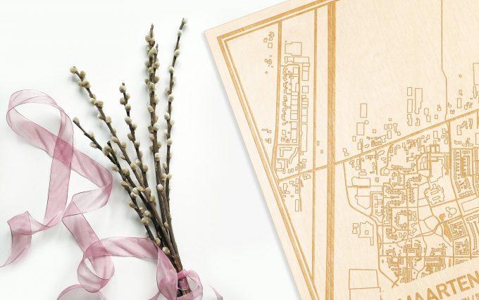 Hier ligt de houten plattegrond Maartensdijk naast een bloemetje als gepersonaliseerd cadeau voor haar.