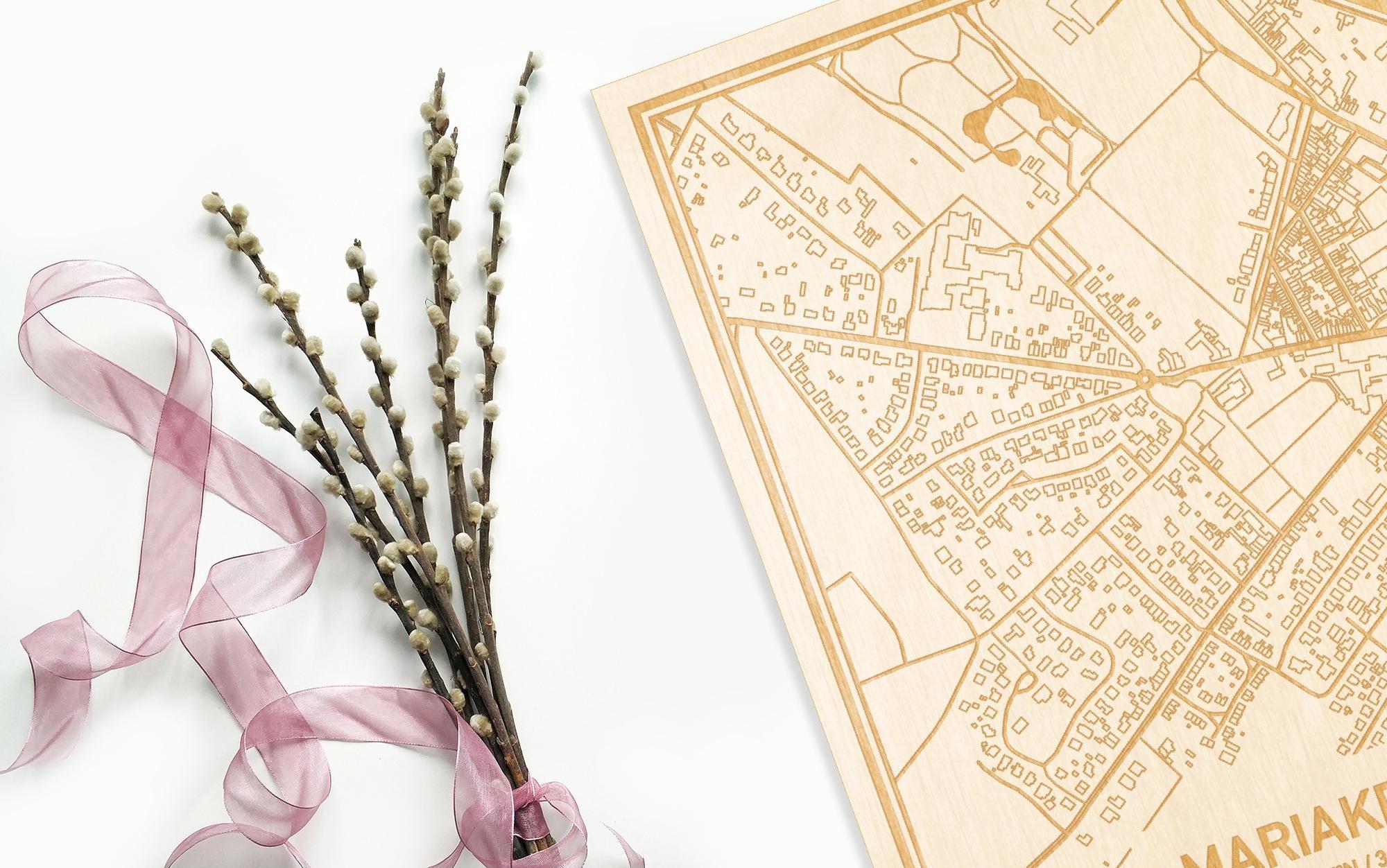 Hier ligt de houten plattegrond Mariakerke naast een bloemetje als gepersonaliseerd cadeau voor haar.