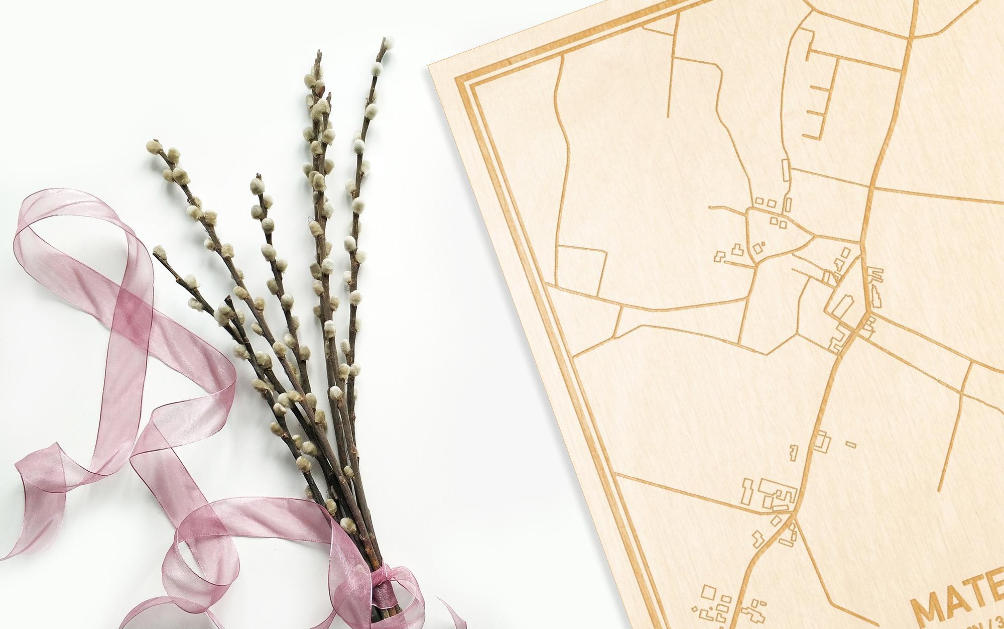 Hier ligt de houten plattegrond Mater naast een bloemetje als gepersonaliseerd cadeau voor haar.