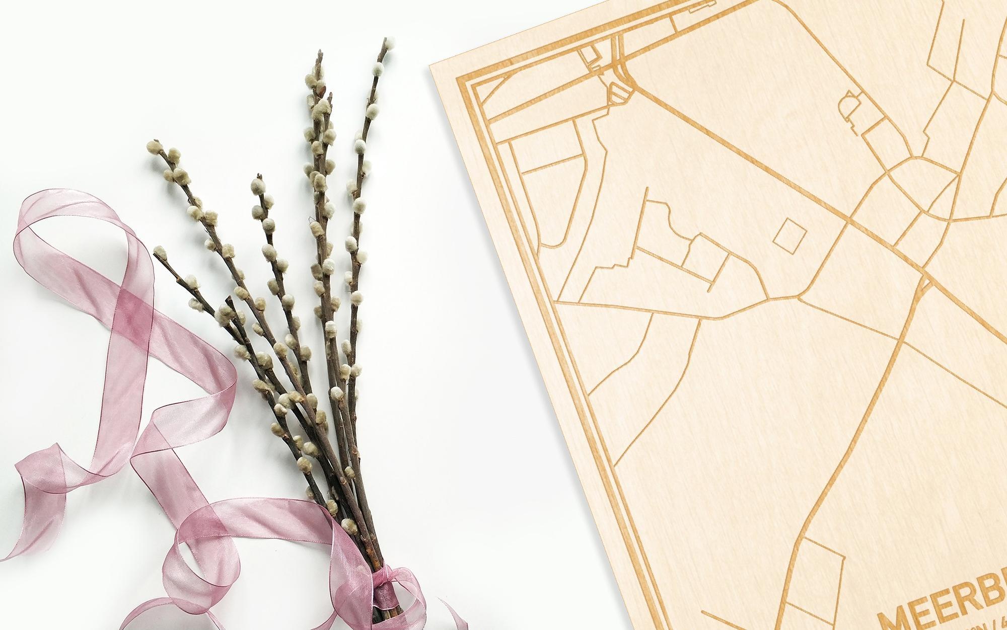 Hier ligt de houten plattegrond Meerbeke naast een bloemetje als gepersonaliseerd cadeau voor haar.