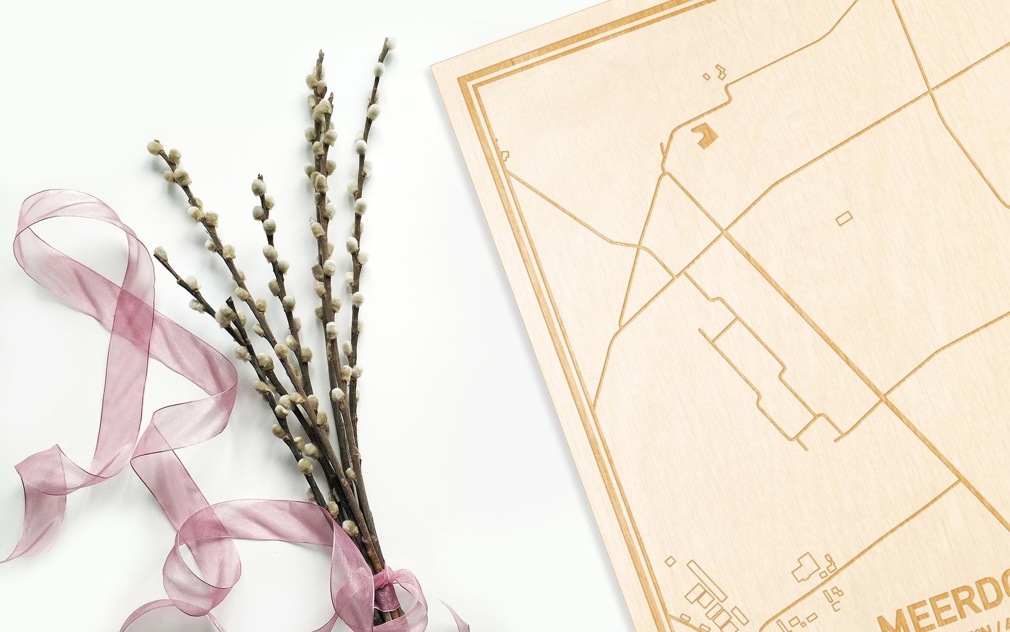 Hier ligt de houten plattegrond Meerdonk naast een bloemetje als gepersonaliseerd cadeau voor haar.