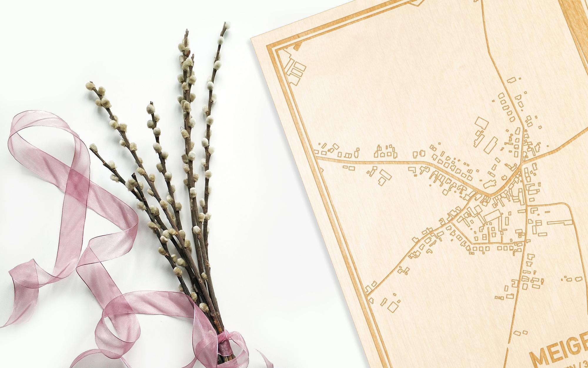 Hier ligt de houten plattegrond Meigem naast een bloemetje als gepersonaliseerd cadeau voor haar.