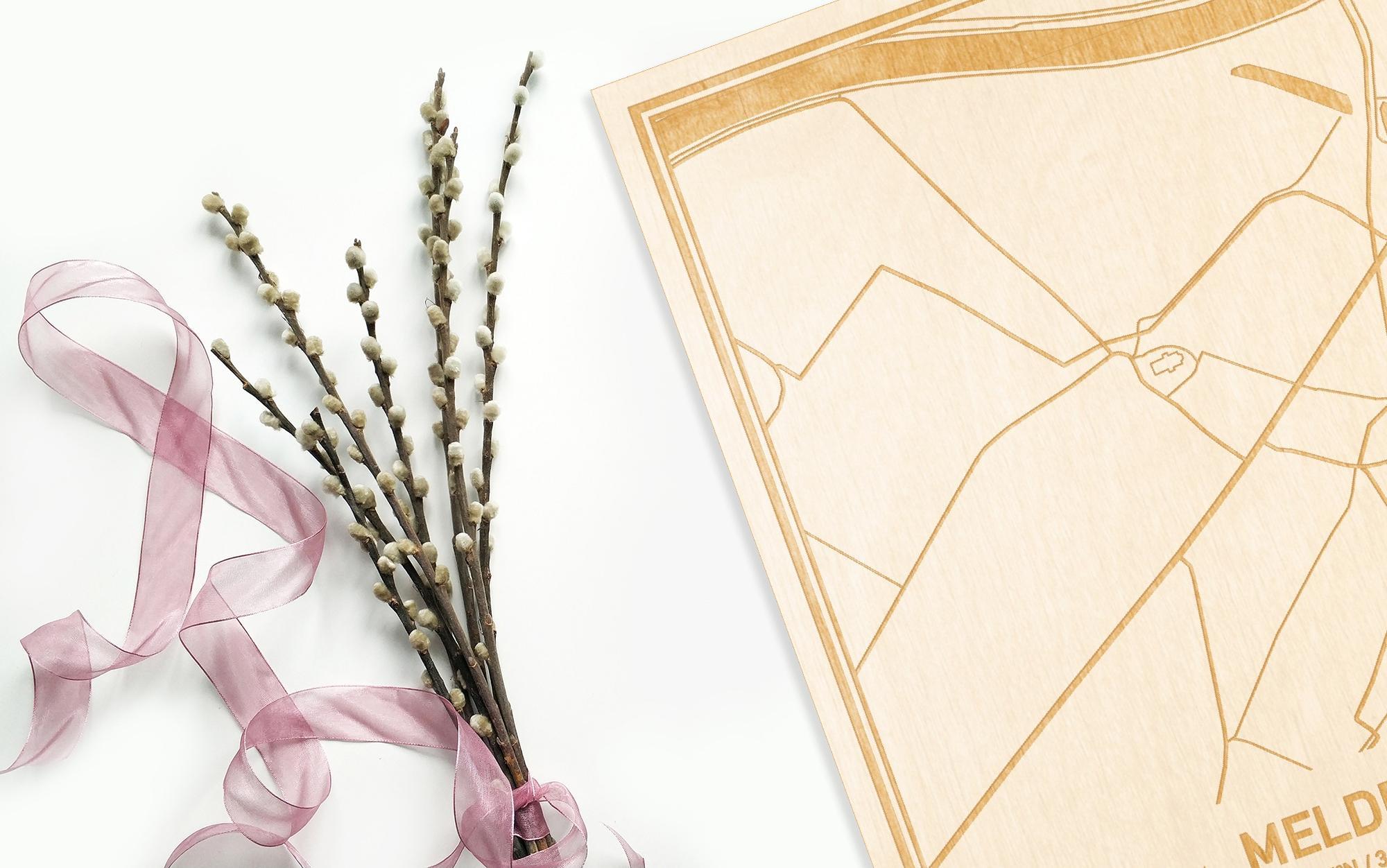 Hier ligt de houten plattegrond Melden naast een bloemetje als gepersonaliseerd cadeau voor haar.