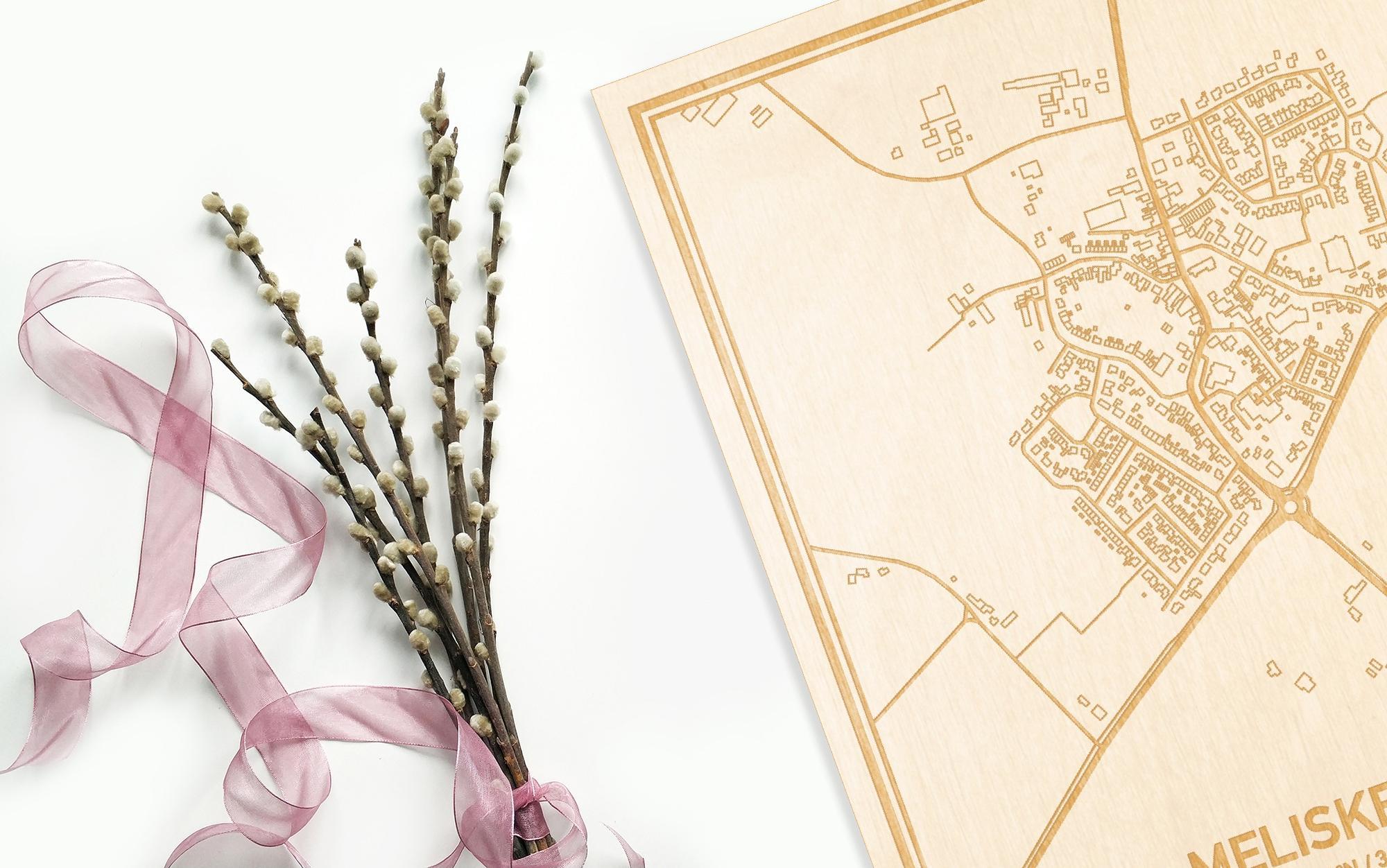 Hier ligt de houten plattegrond Meliskerke naast een bloemetje als gepersonaliseerd cadeau voor haar.